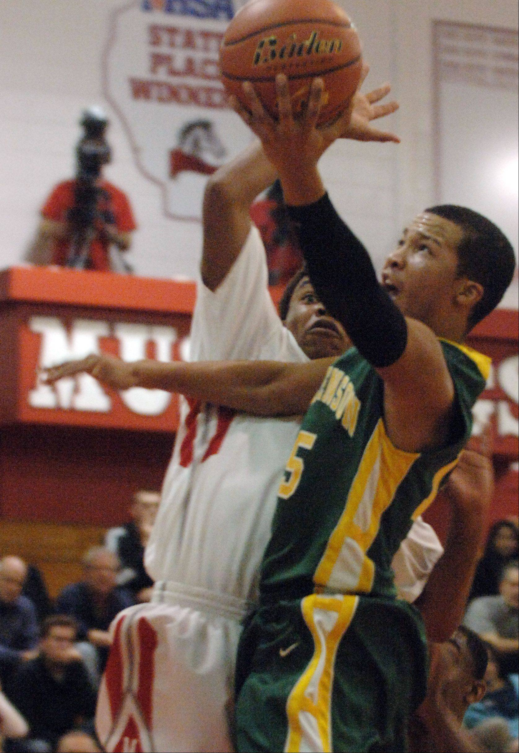 Stevenson's Jalen Brunson, right, heads to the hoop past Mundelein's Cliff Dunigan Friday night in Mundelein.