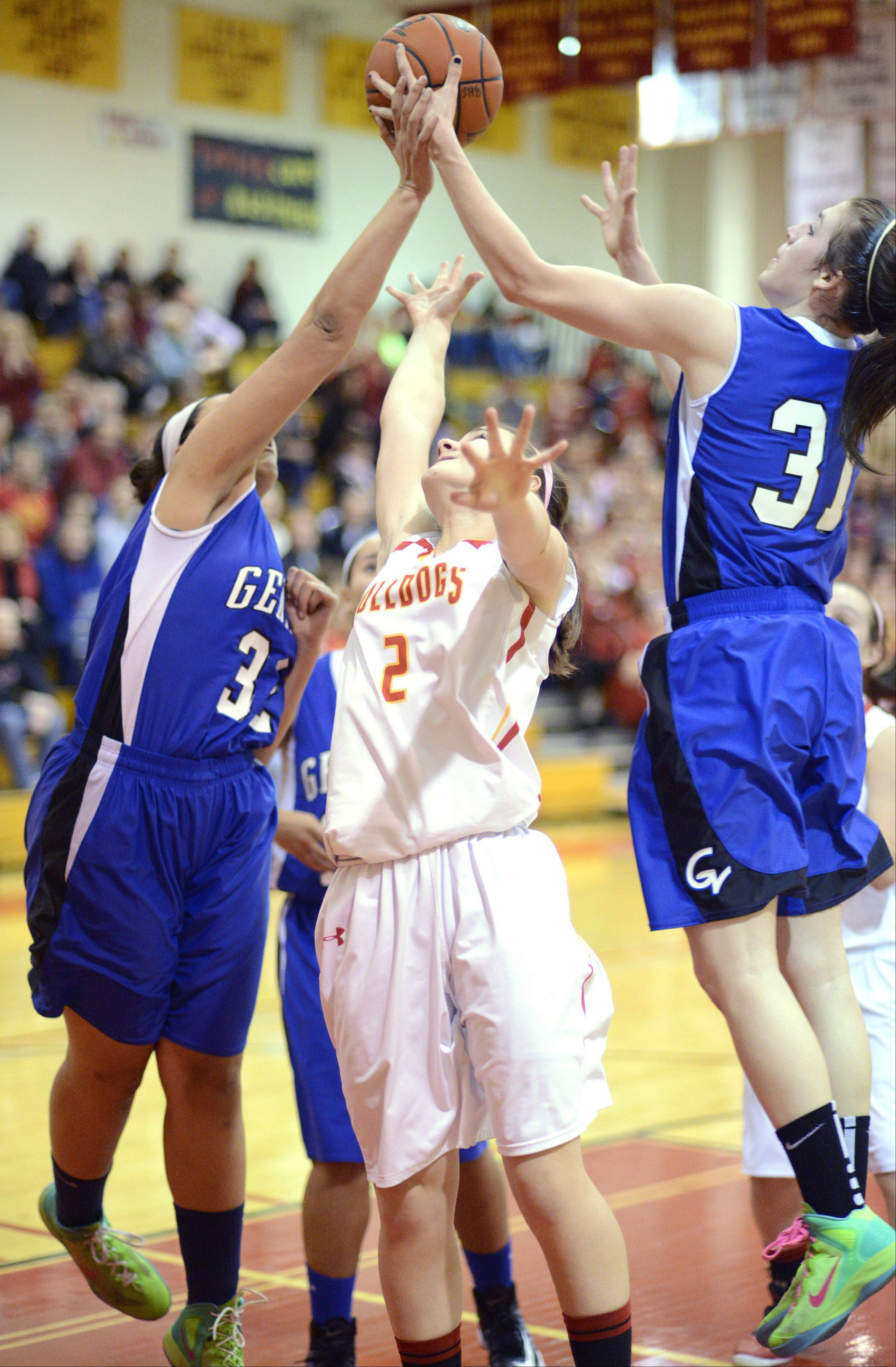 Laura Stoecker/lstoecker@dailyherald.com Geneva's Sidney Santos, left, and Sami Pawlak leap for a rebound keeping it out of reach of Batavia's Grace Andrews in the second quarter on Friday, January 11.
