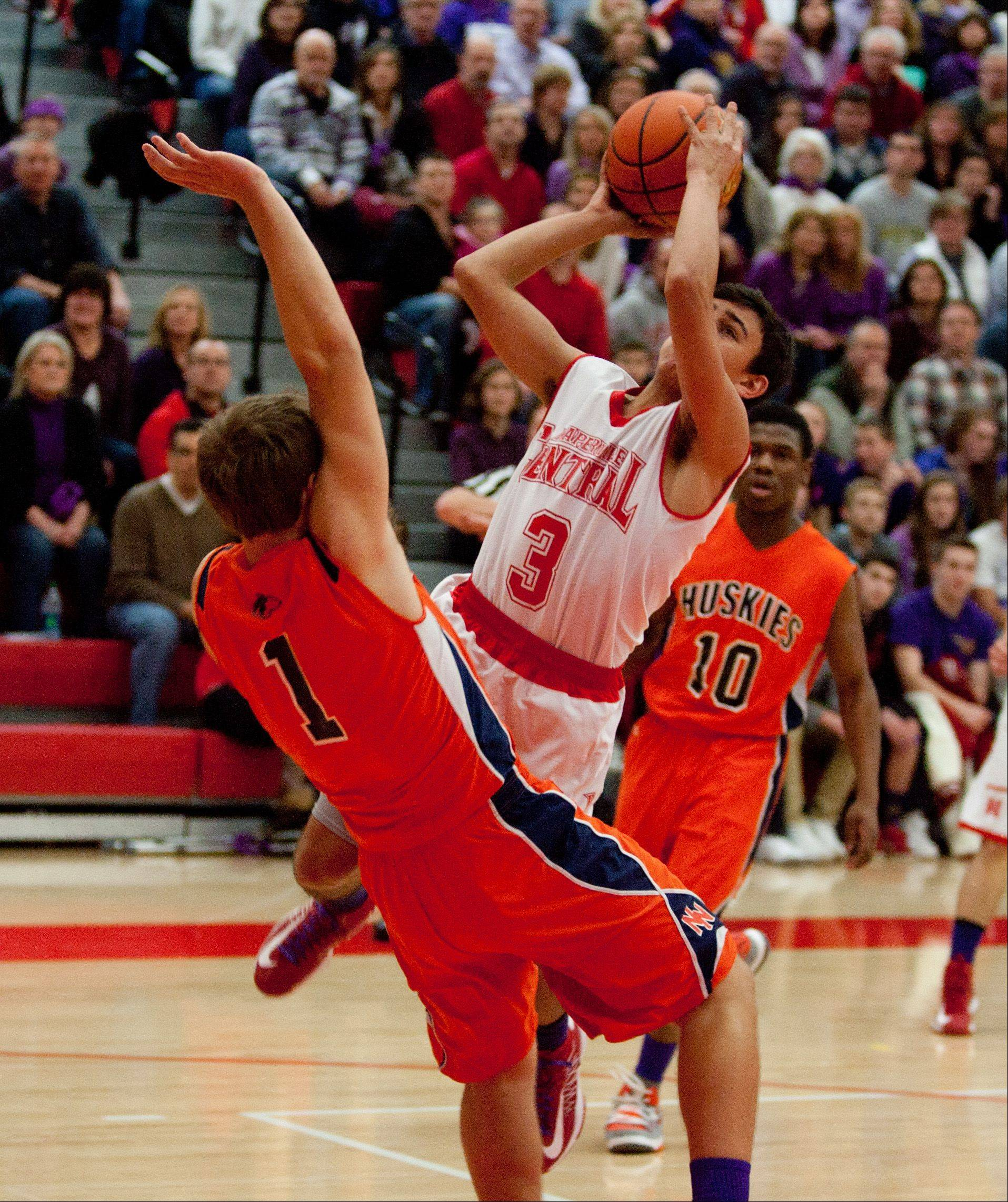 Naperville Central's Nicky Lopez collides with Naperville North's Derek Westman .