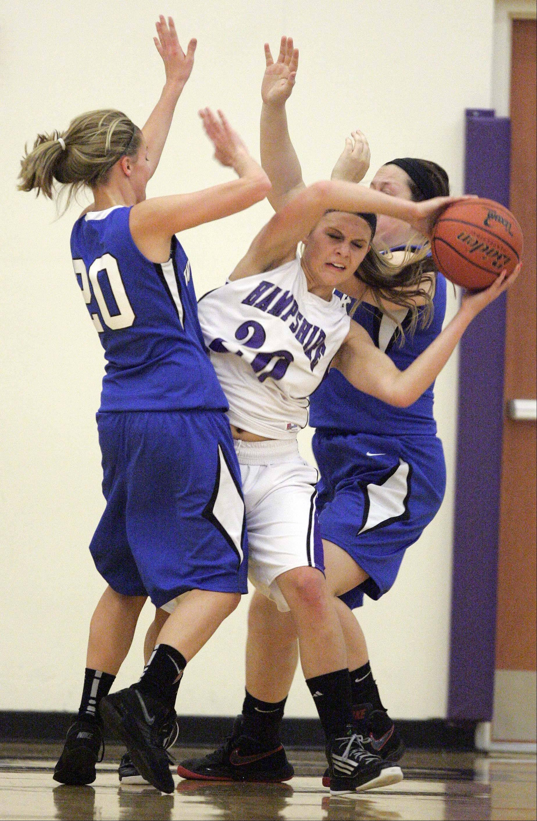 Hampshire's Lizzy Panzica (20) slips between Woodstock's Sydney Haulotte and Amber Roberts (44) Saturday at Hampshire..