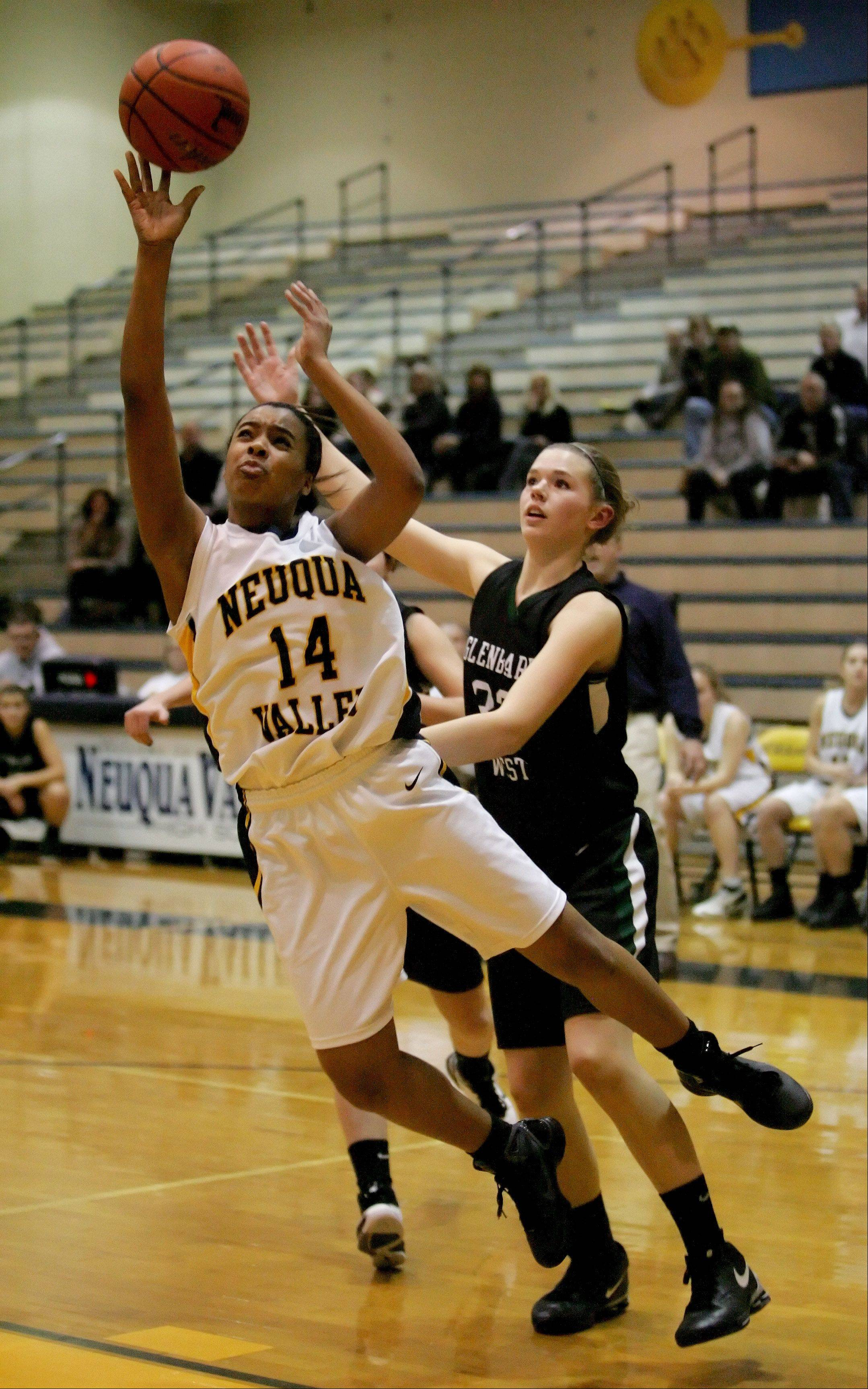Najee Smith of Neuqua Valley moves in front of Ellen Nighbor of Glenbard West to make a basket in girls basketball action Tuesday in Naperville.