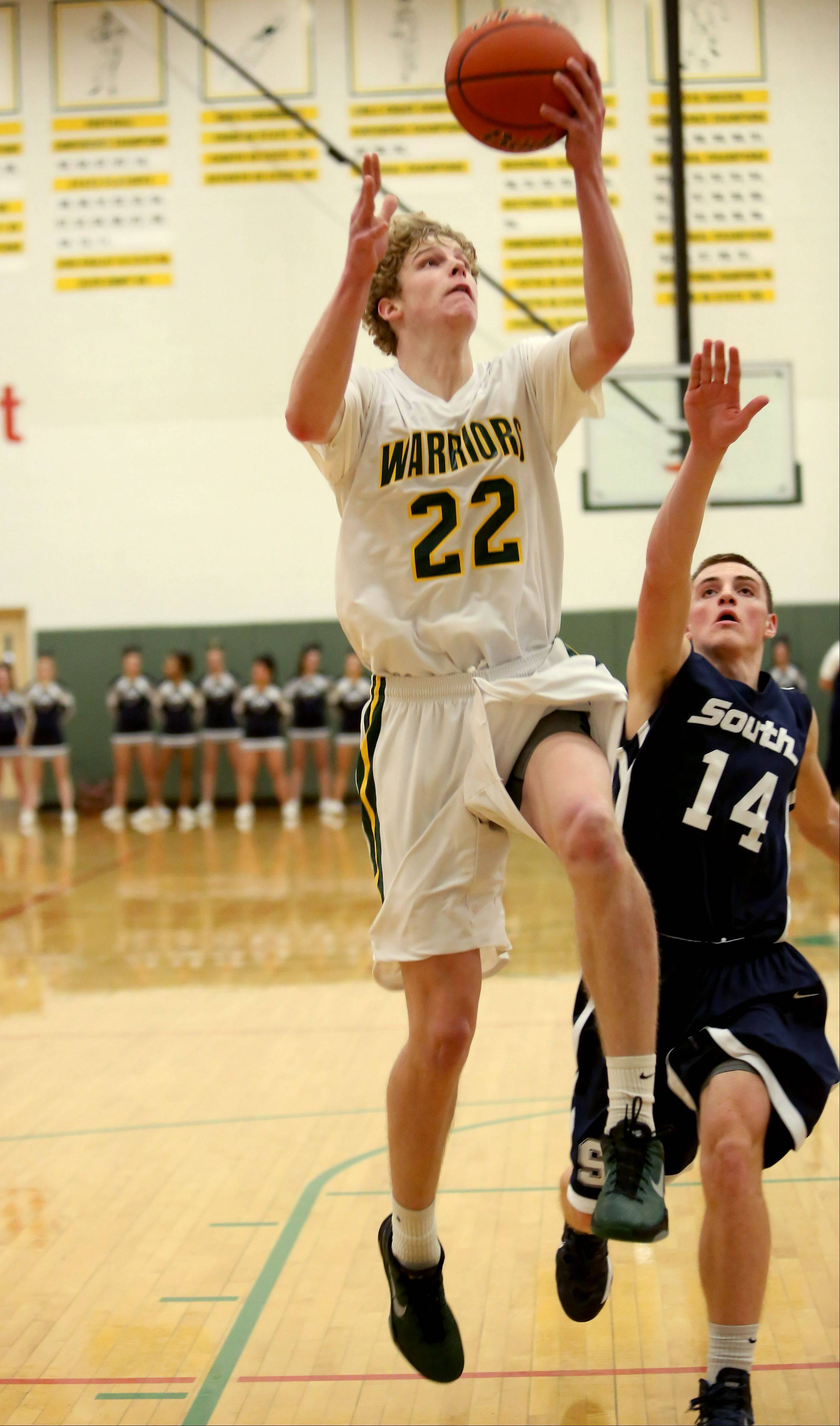 Jack Cordes of Waubonsie Valley, left, goes up for two points as Daylon Edwards ofPlainfield South defends in boys basketball action on Tuesday in Aurora.