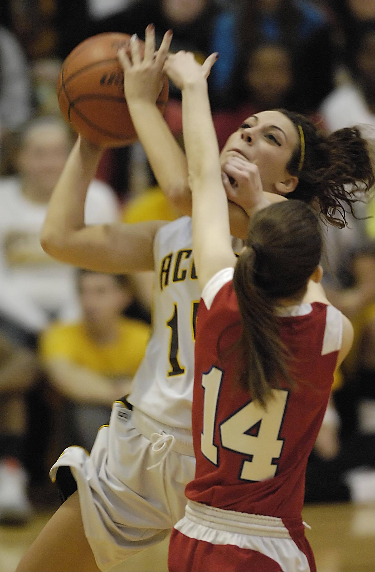 Jacobs' Payton Berg shoots around Dundee-Crown's Melissa Barker Tuesday in Algonquin.