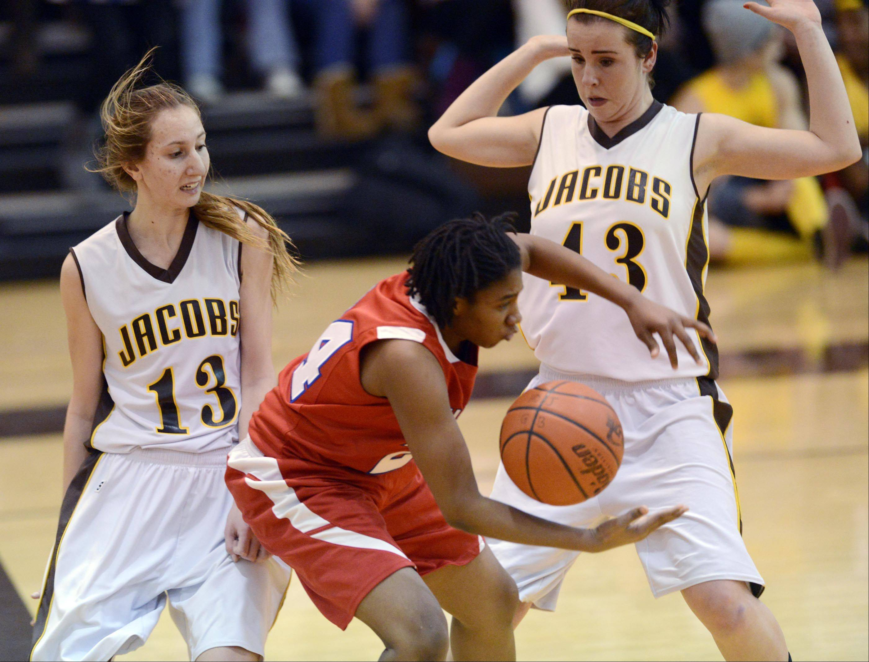 Dundee-Crown's Jereneka Baker loses control of the ball under pressure from Jacobs' Victoria Tamburrino and Jackie Bartolai, right, Tuesday in Algonquin.