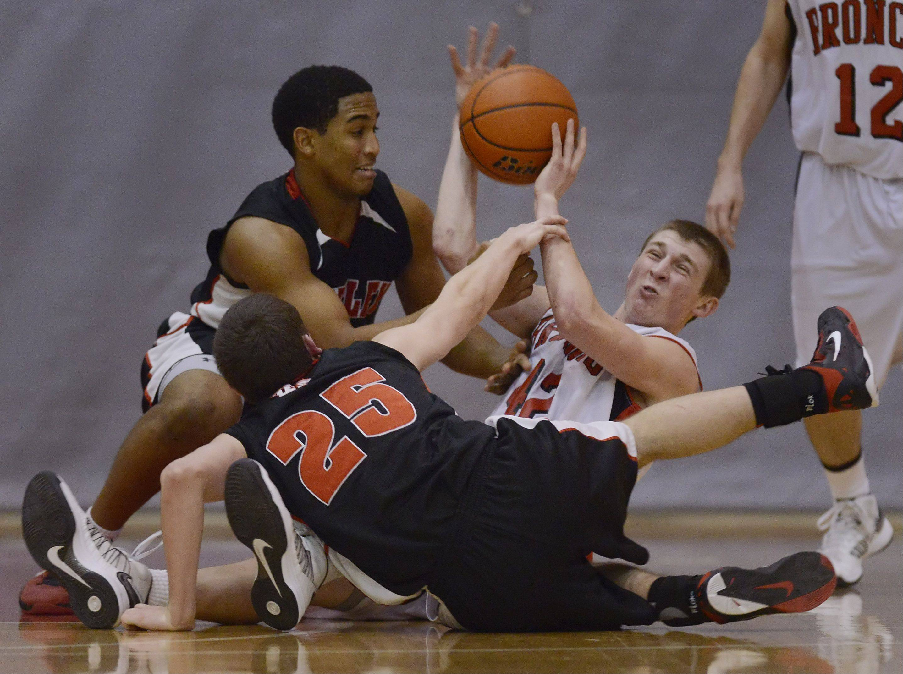 Barrington's Robby Vollman, right, manages to pass the ball to a teammate after diving to the floor with Huntley's Bryce Only, left, and Jason Shields.