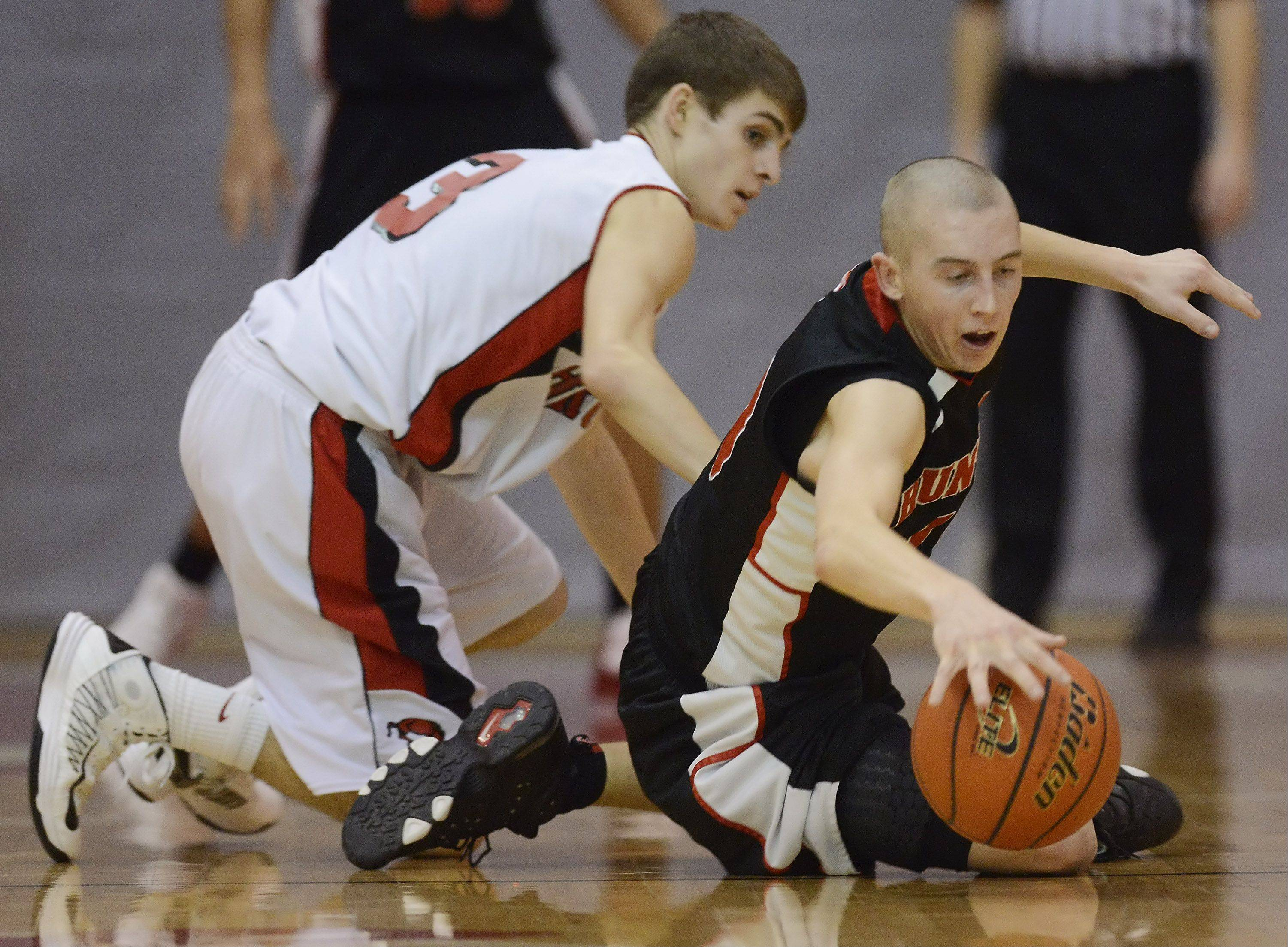 Huntley's TJ Adams, right, dives to the floor for a loose ball in front of Barrington's Brad Zaumseil.