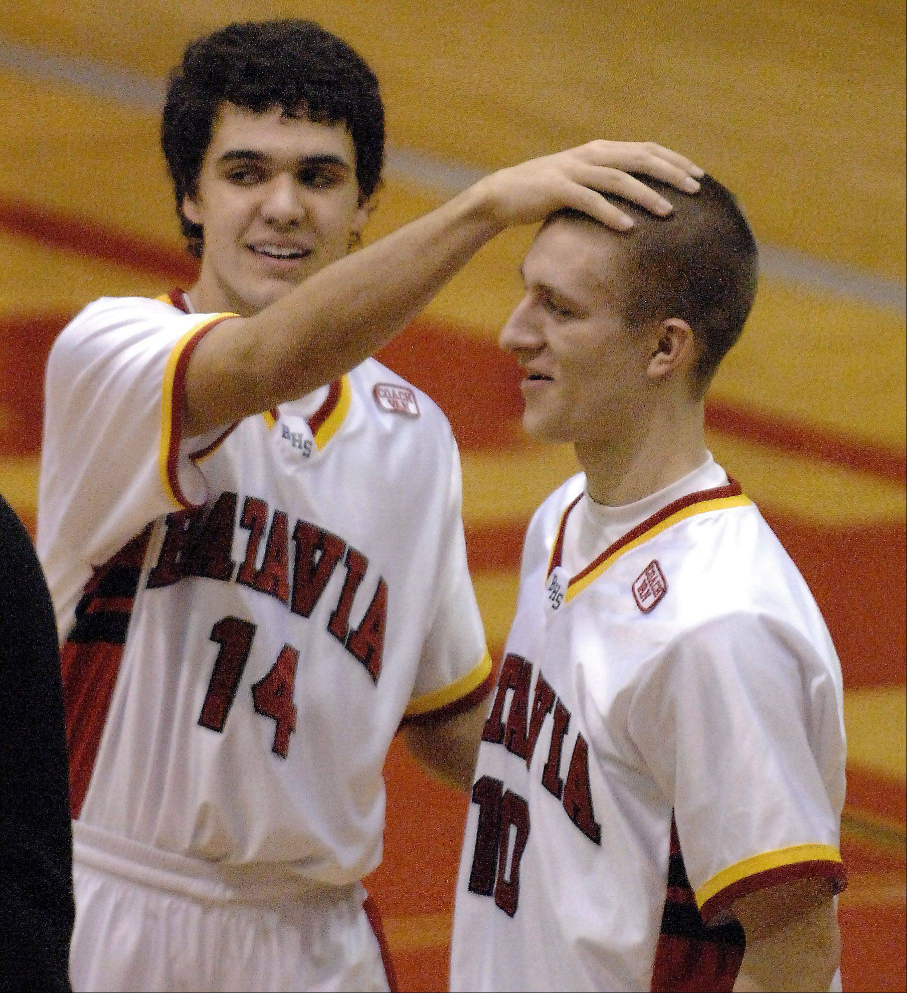 Batavia's Mike Rueffer gets a congratulatory pat on the head from teammate Micah Coffey after a win over Elgin .