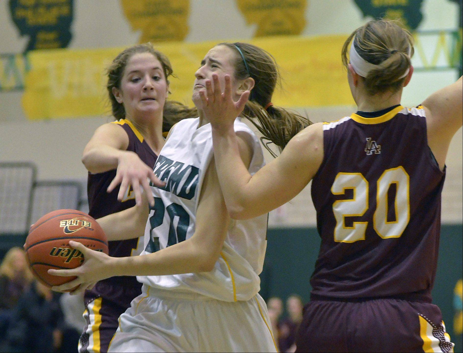 Fremd's Haley Gorecki (20) draws the foul in the fourth quarter as she is defended by Loyola Academy's Maggie Nick (12) and Egan Berne (20)
