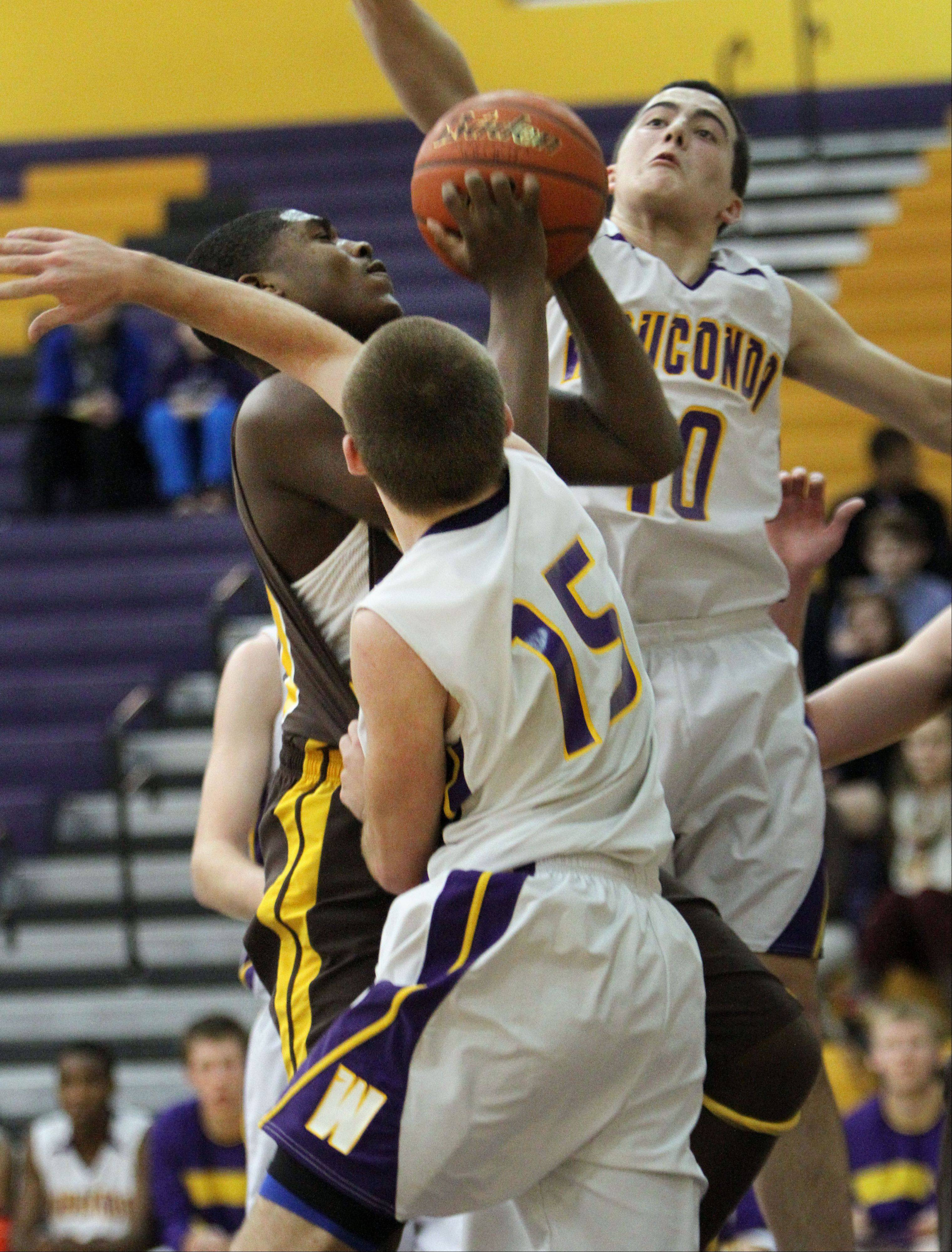 Carmel's Nickai Poser, left, drives on Wauconda's Austin Swenson and Keith Blomberg on Wednesday night in Wauconda.