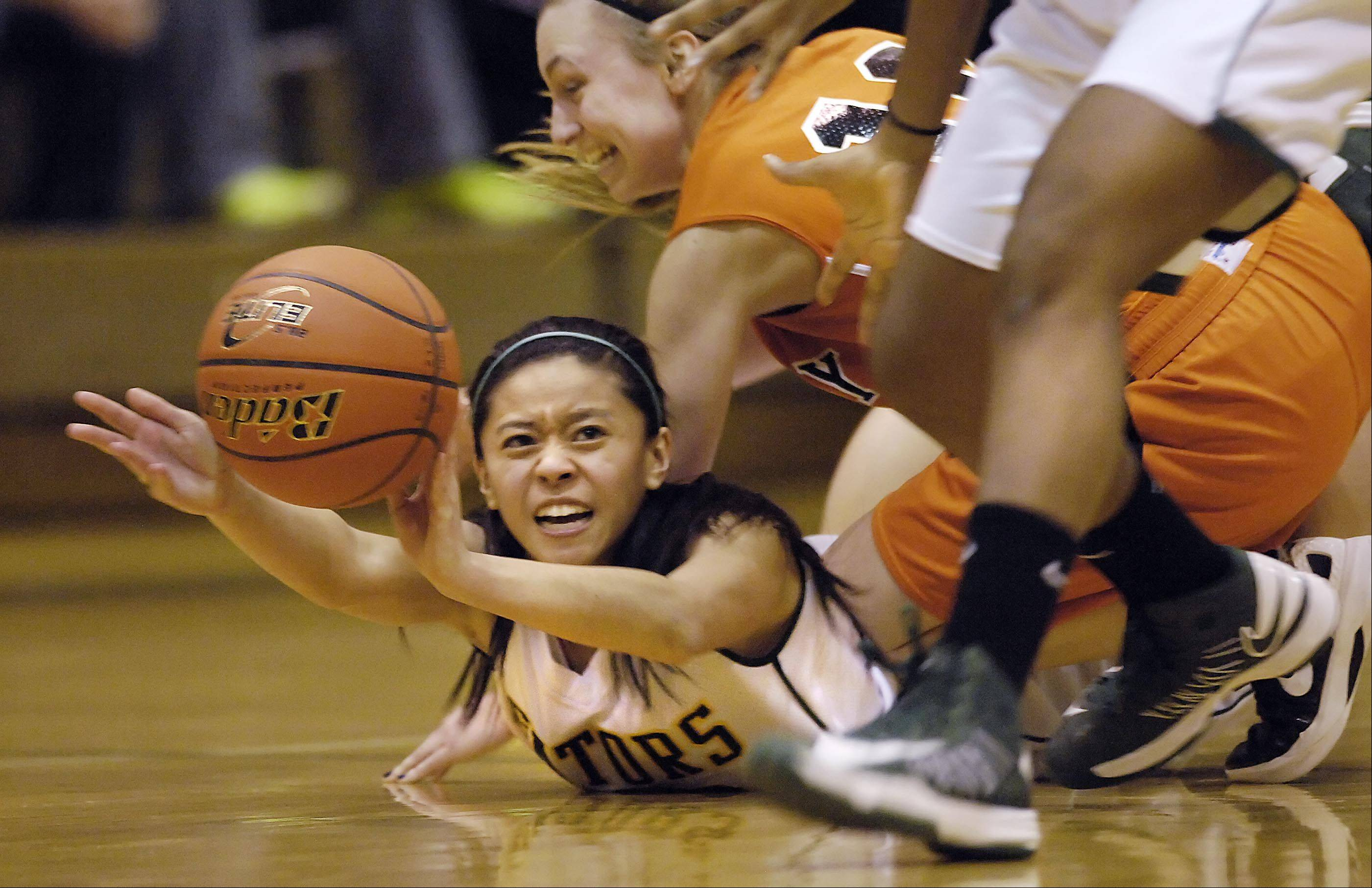 Crystal Lake South's Gaby De Jesus passes to teammate Kianna Clark as McHenry's Laura D'Angelo falls on her back.