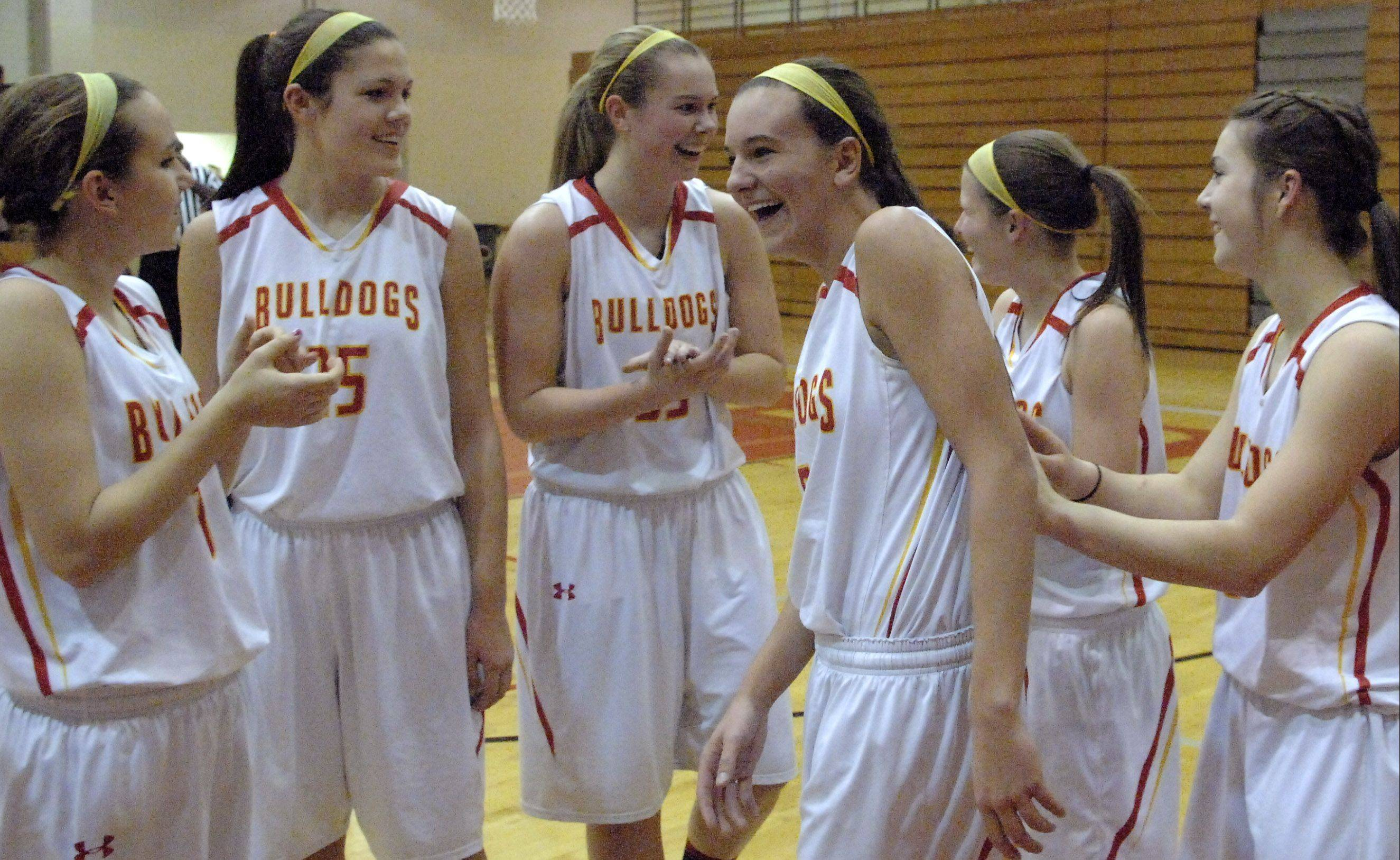 Batavia teammates cheer for Liza Fruendt, center, after she scored her 1,000th career point Thursday against Larkin at Batavia.