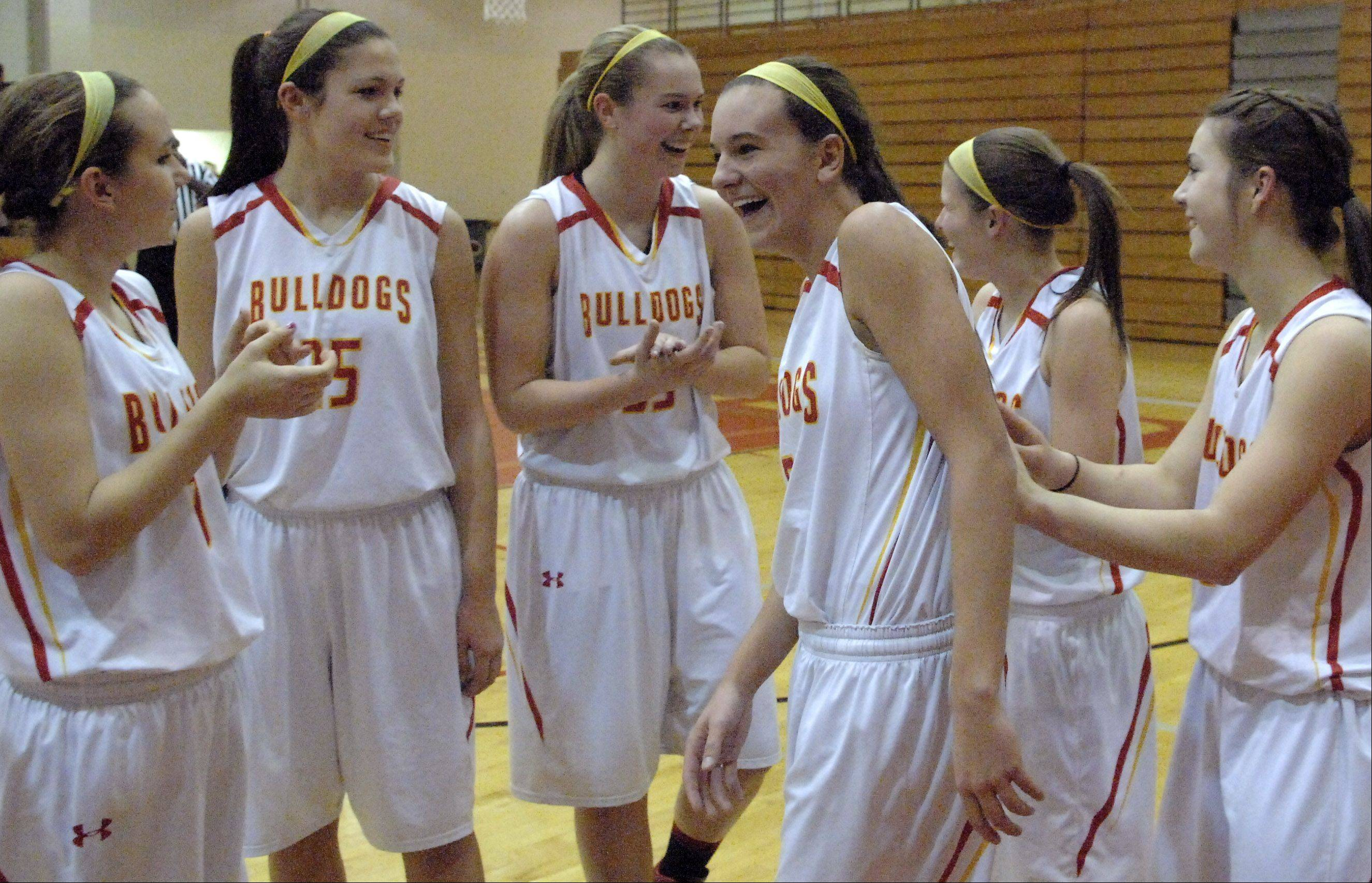Batavia teammates applaud for Liza Fruendt, center, during a time out following her 1000th career point.