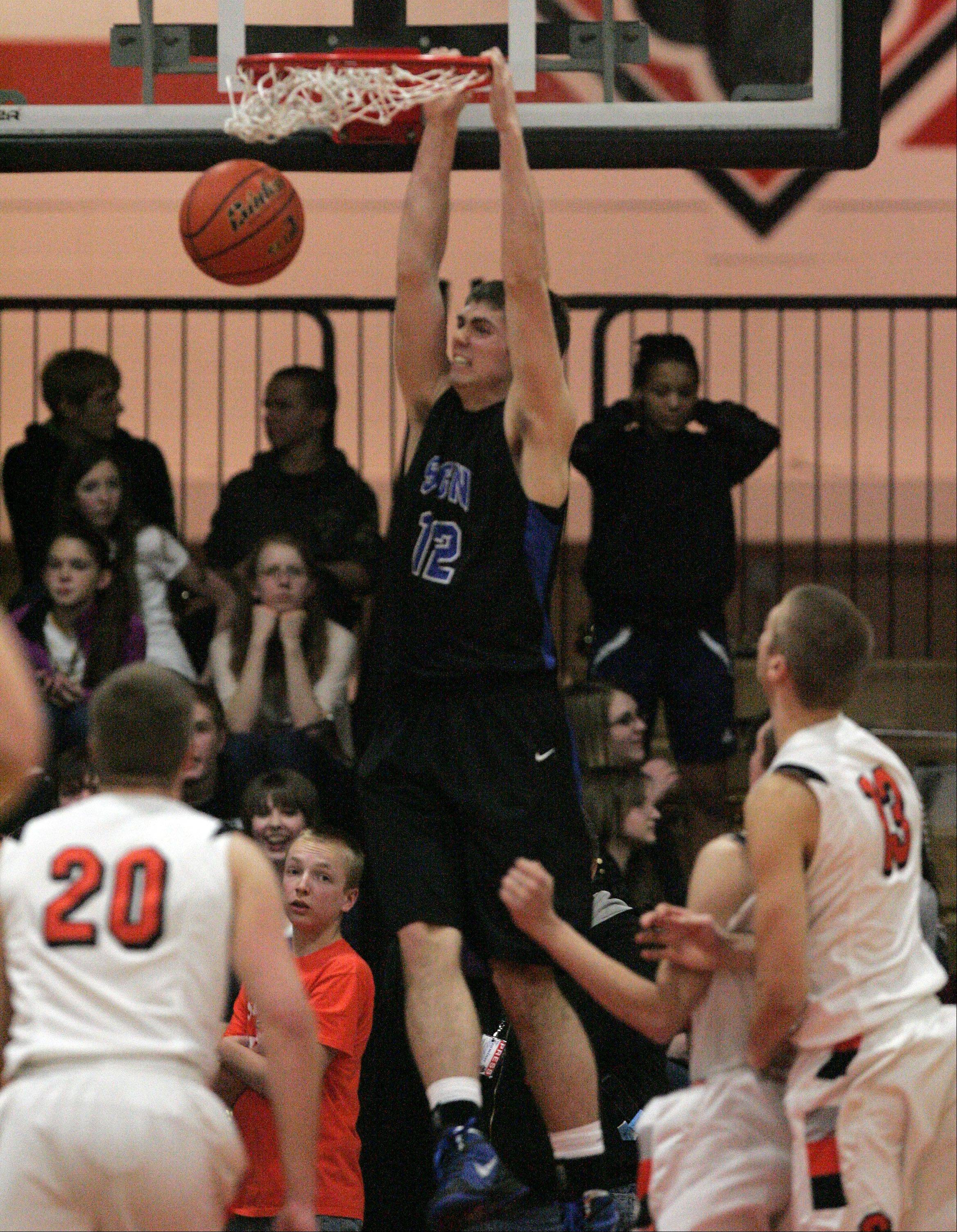 St. Charles North's Quinten Payne, 12, throws home a dunke at St. Charles East during boys basketball Friday January 18, 2013.