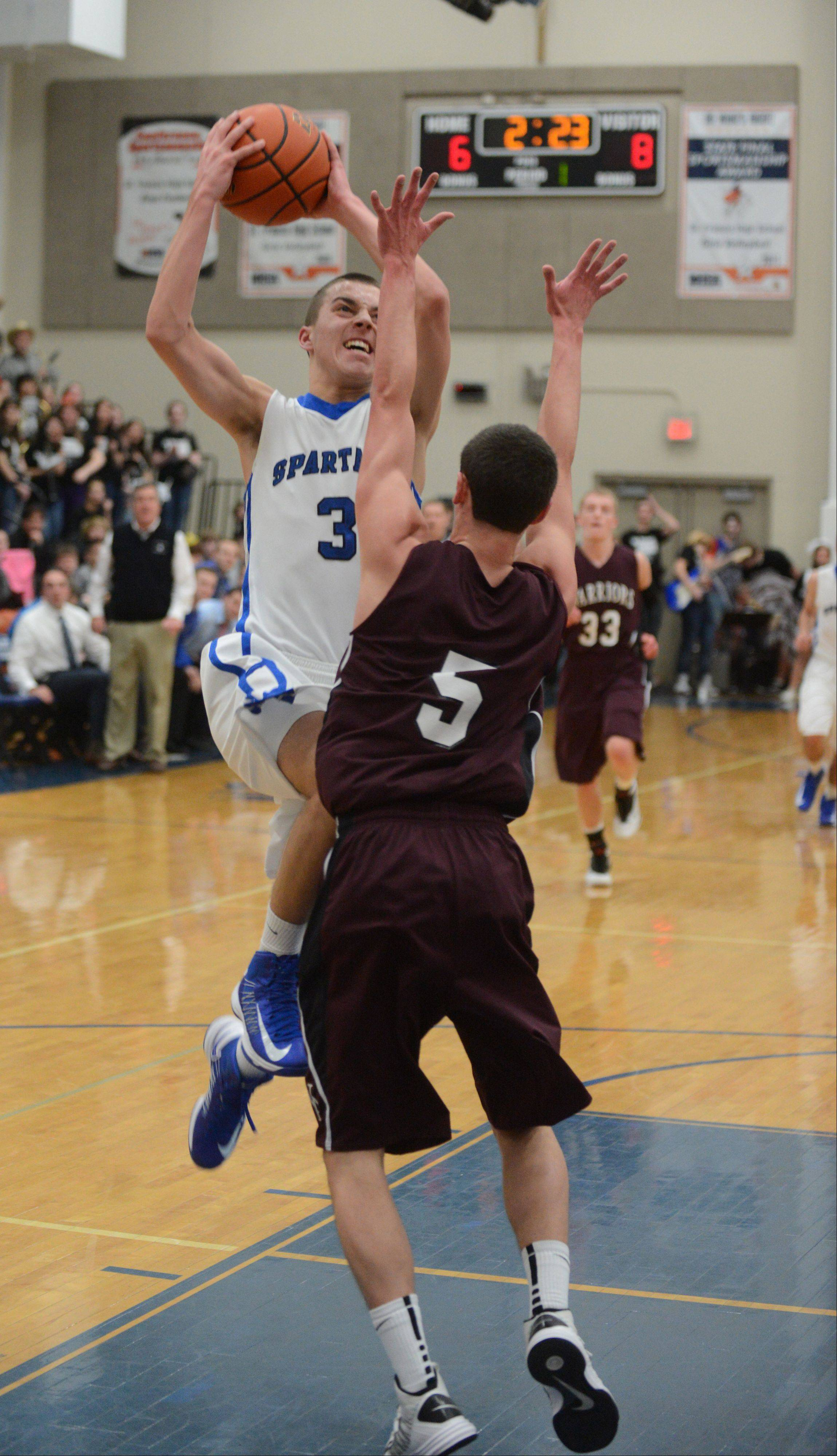 Jason Pisarski of St. Francis,left, takes one to the net over Collin Roy of Wheaton Academy.