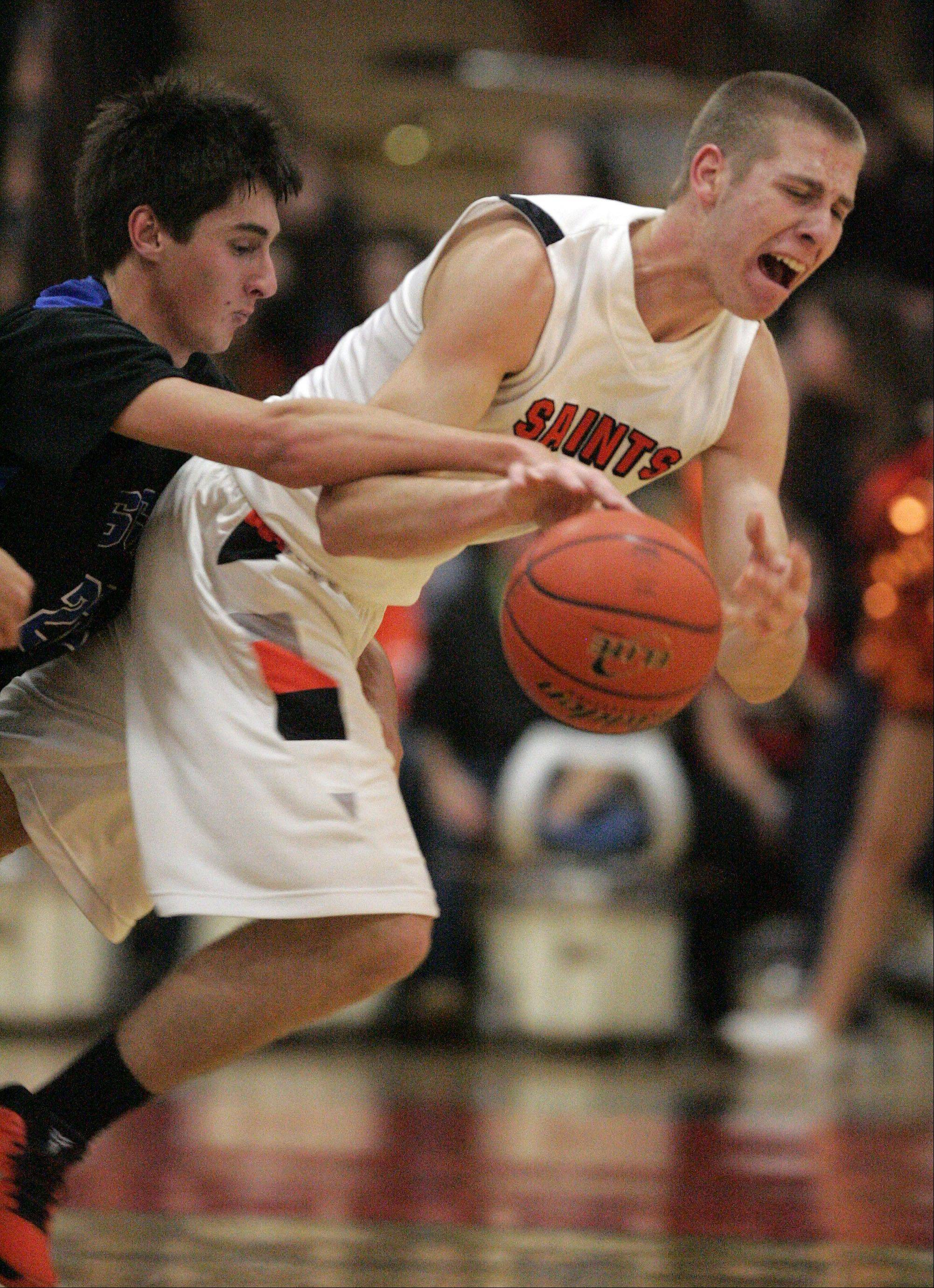 St. Charles North's Kyle Swanson and St. Charles East's Ben Skoog battle for control of a loose ball.