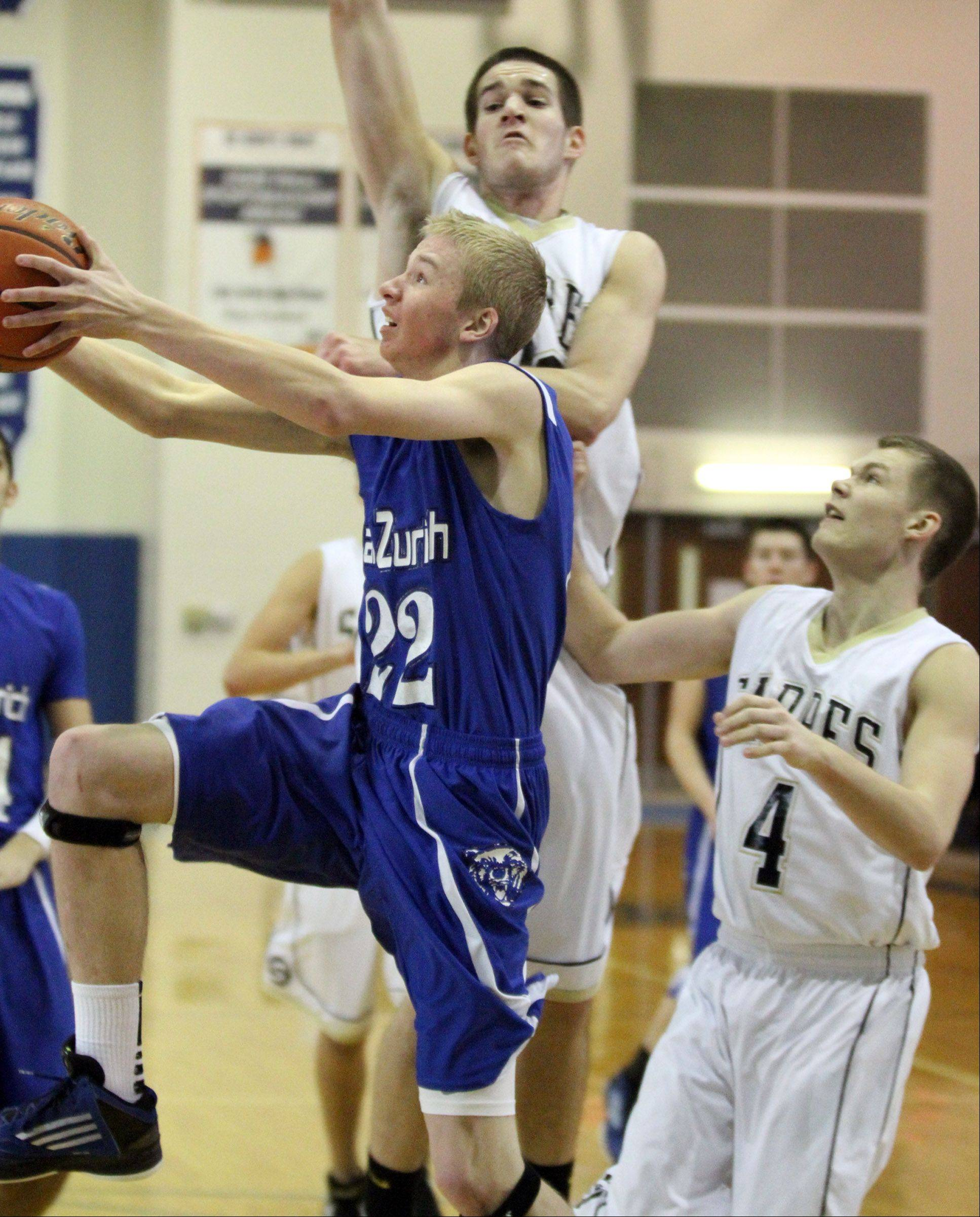 Lake Zurich guard Brad Kruse shoots under the basket past Streamwood defenders Zack Harris, center, and Jacob Siewert at Lake Zurich on Saturday.