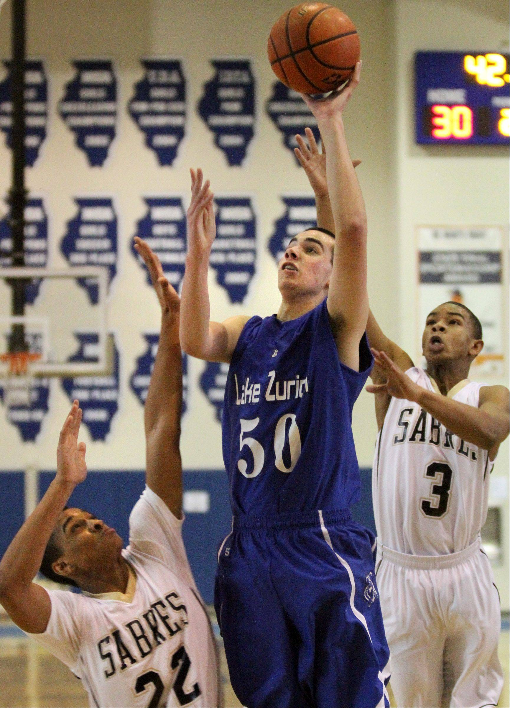 Lake Zurich center Will McClaughry shoots over Streamwood defenders Kyle Strong, left, and Trevious Norman at Lake Zurich on Saturday.