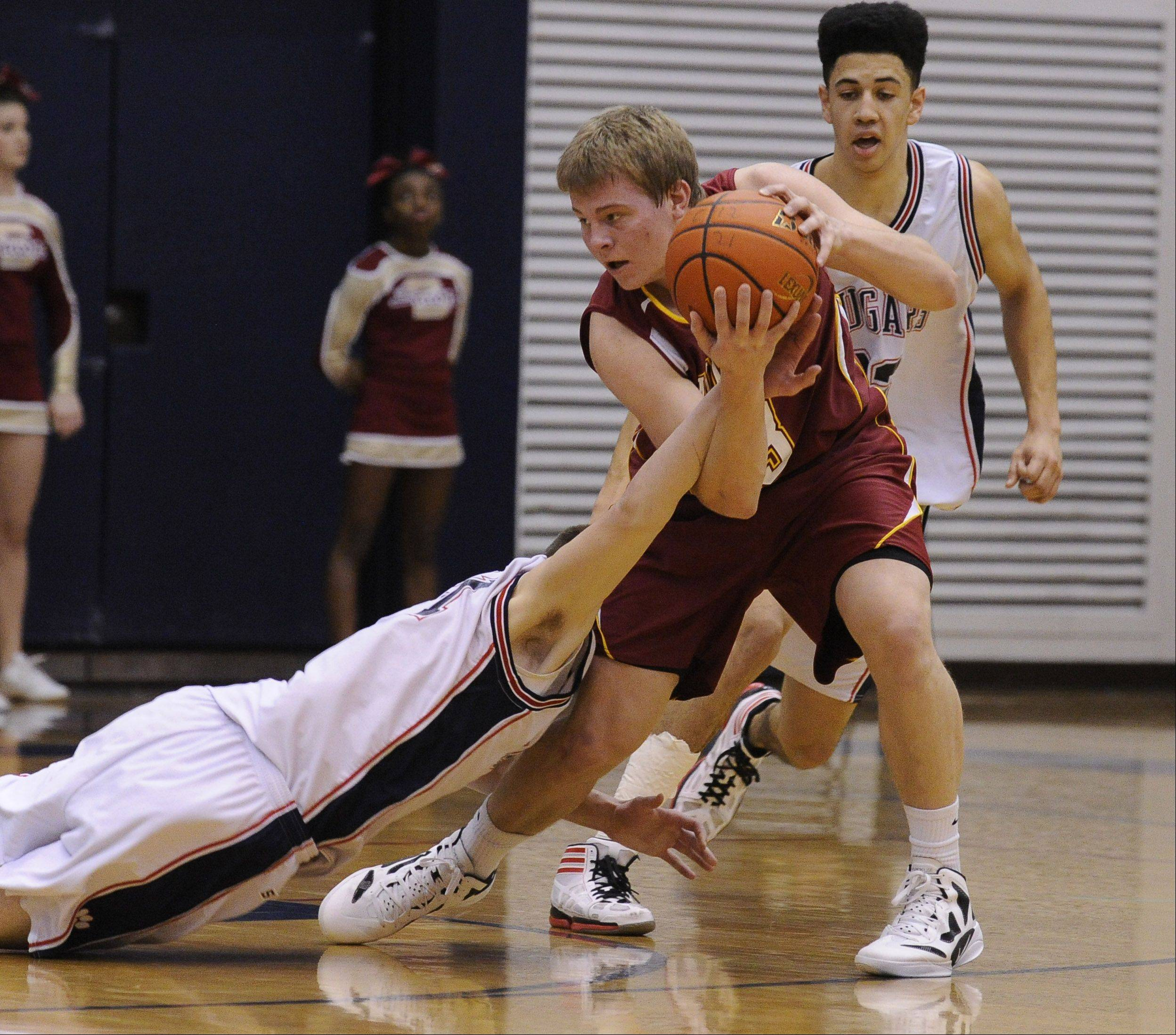 Conant's Ryan Blaha tries to strip the ball from Schaumburg's Kyle Bolger at Conant on Saturday.