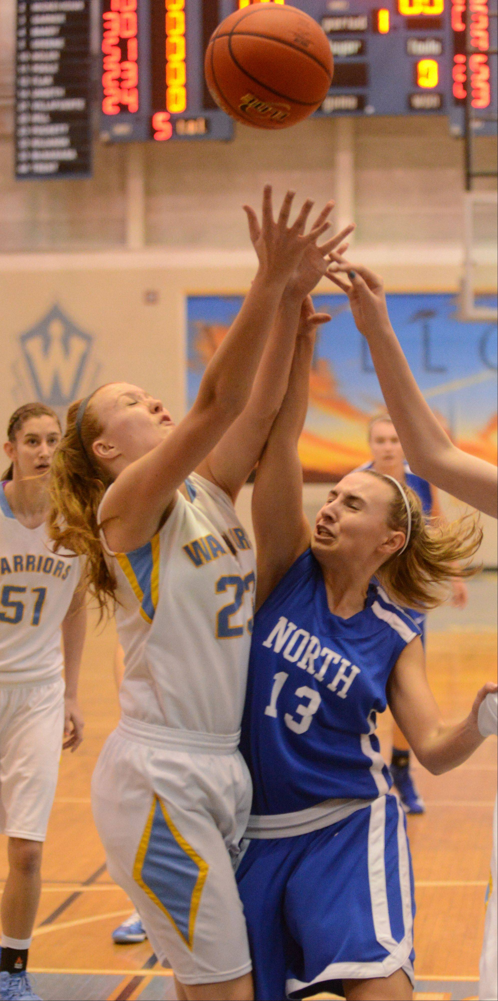Ashley Collins of Main West,left, and Brooke Schanowski of Wheaton north go for a rebound during the Wheaton North vs. Maine West girls basketball game at McDonald's Shootout in Willowbrook Saturday.