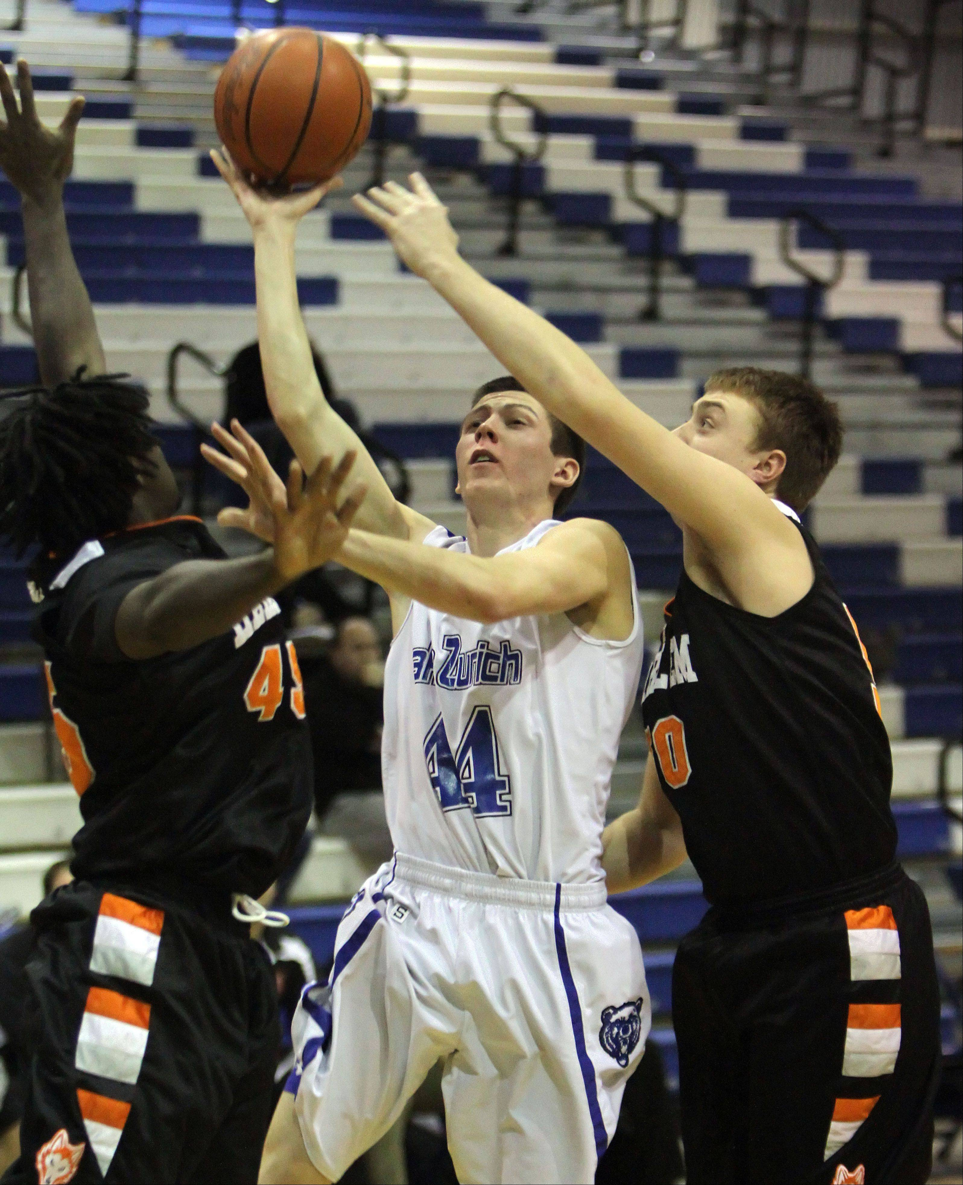 Lake Zurich's Ryan Roach drives on Brent Croft, left, and Harlem on Monday night at Lake Zurich.