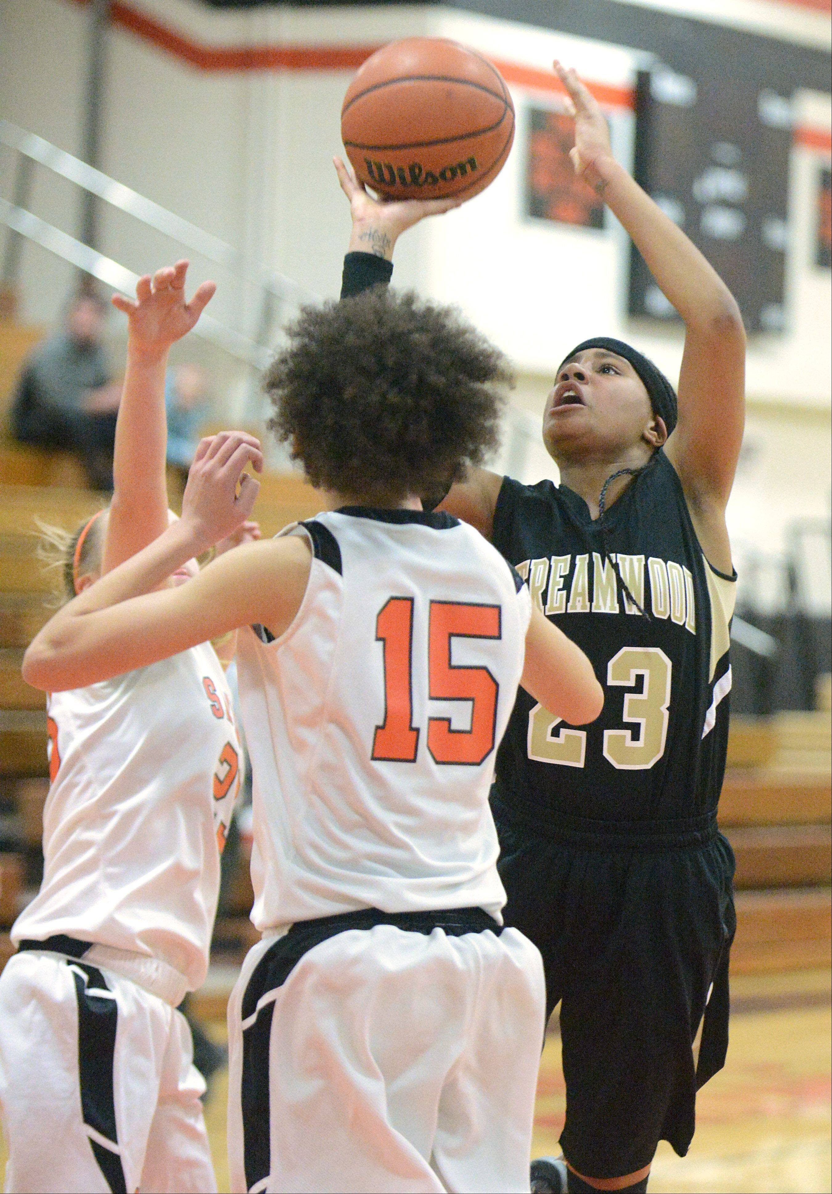 Streamwood's Deja Moore shoots past a block by St. Charles East's Amanda Hilton, left and Kyra Washington in the second quarter on Tuesday, January 22.