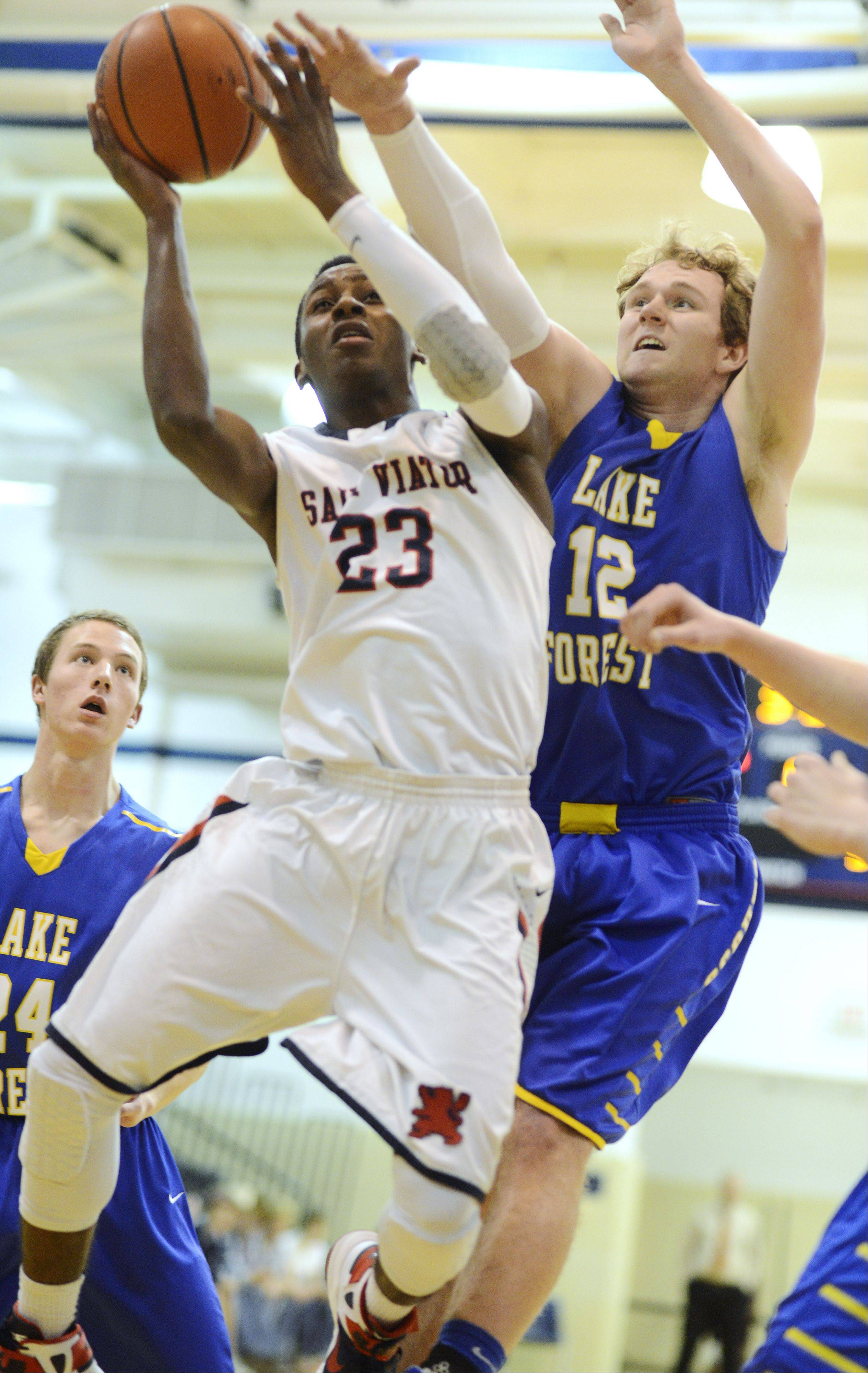 St. Viator's Ore Arogundade drives to the basket against Lake Forest's Evan Boudreaux during Tuesday's game.