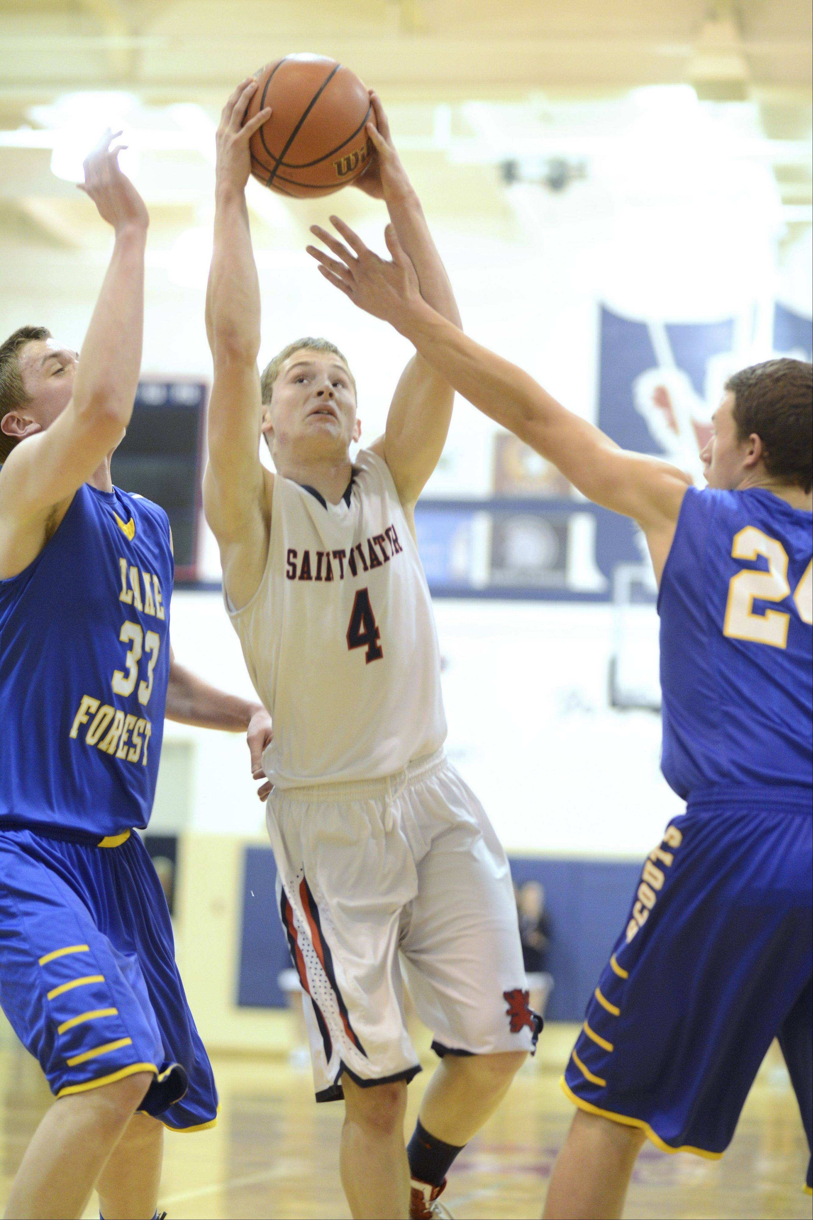 St. Viator's Kevin Hammarlund drives to the basket between Lake Forest's Sam Downey, left, and Cal Miller.