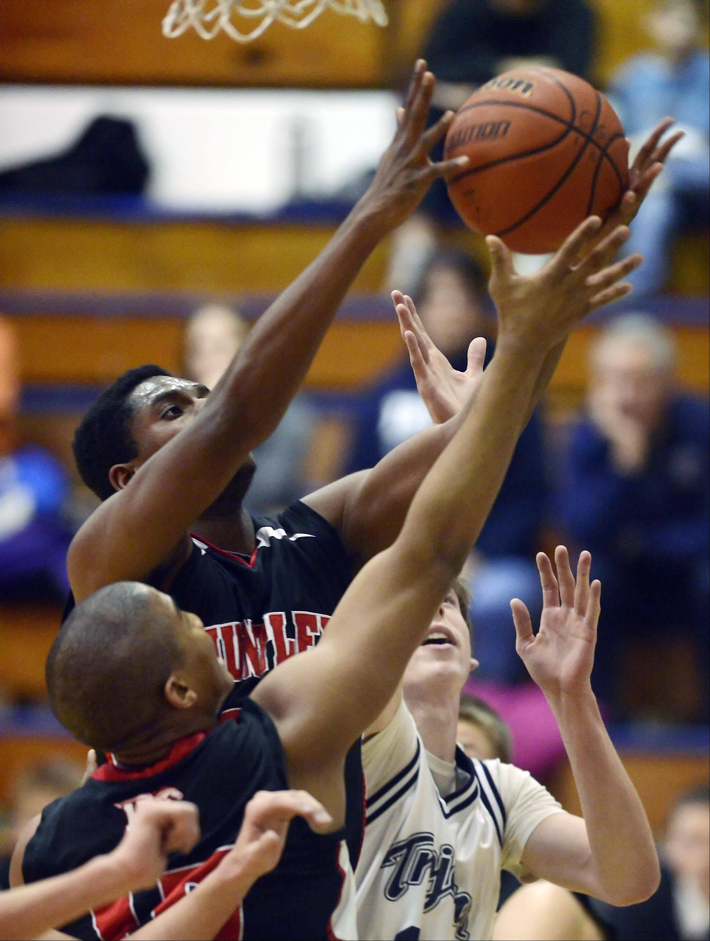 Huntley's Amanze Egekeze takes a rebound against teammate Bryce Only and Cary-Grove's Dean Lee .