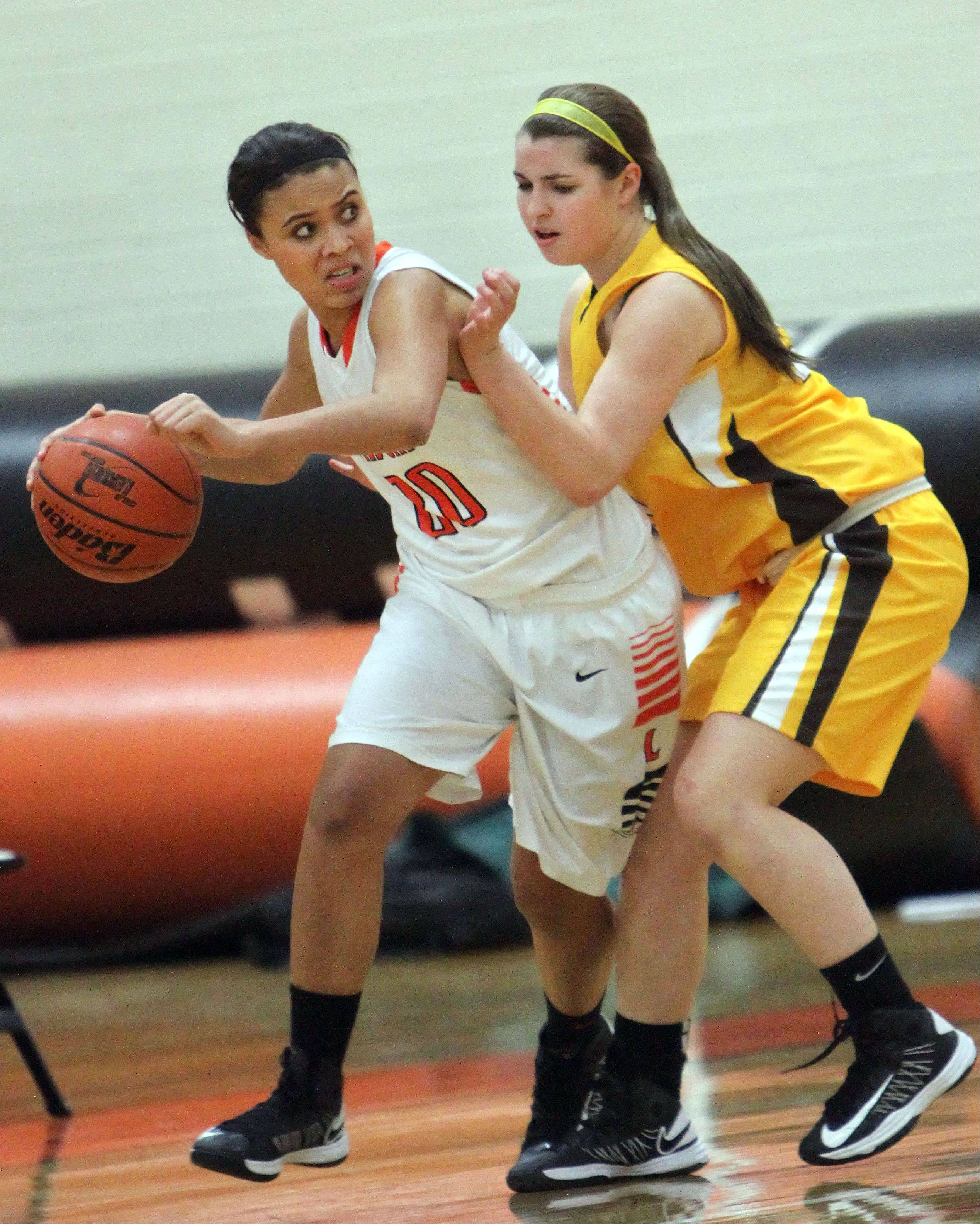 Libertyville's Jenna Slobodnik, left, drives on Carmel's Alexa Svoboda on Wednesday night at Libertyville.