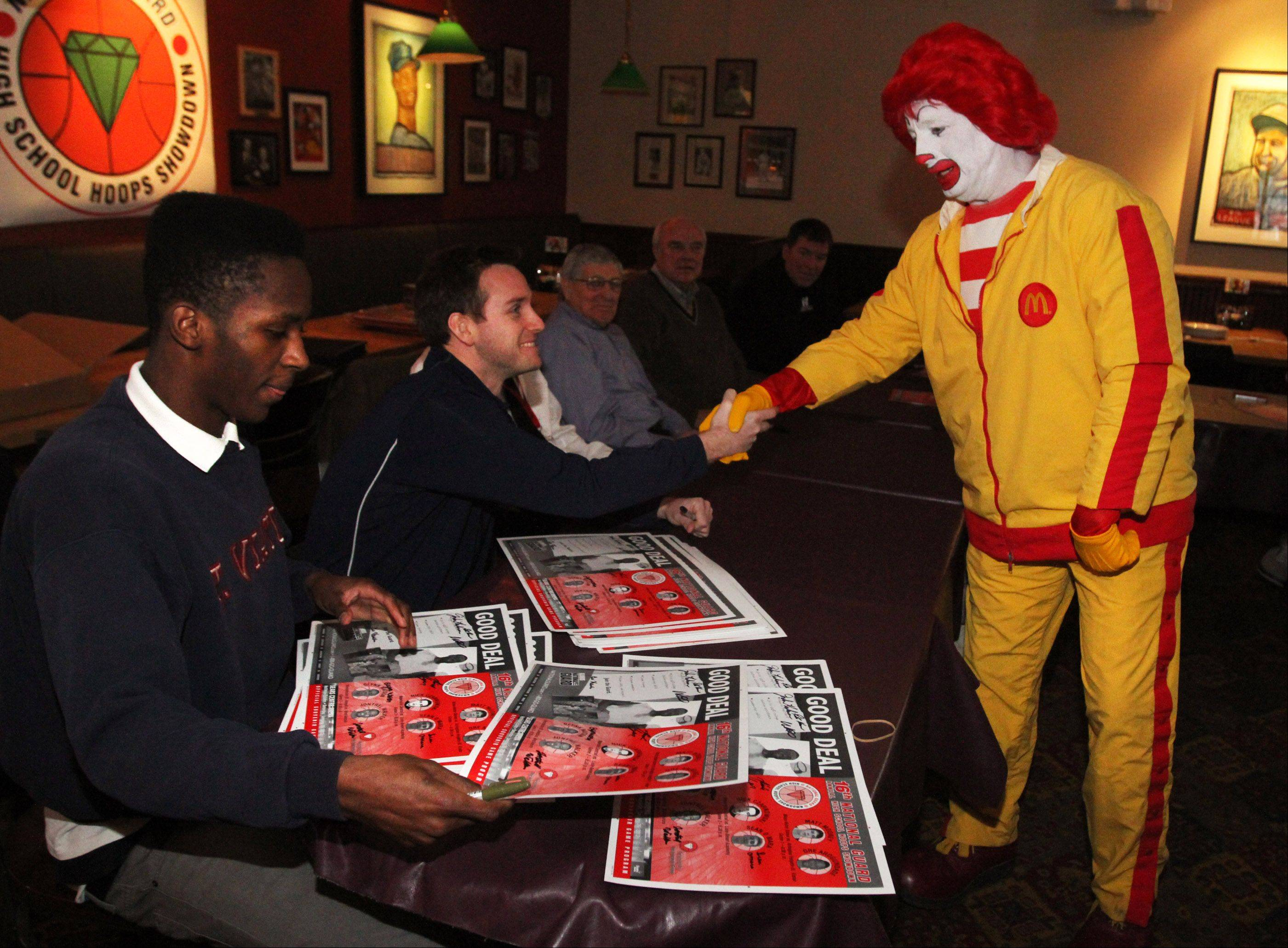 St. Viator boys basketball coach Mike Howland gets a hand from Ronald McDonald as Lions guard Arogundade signs posters during a news conference at Lou Malnati's Pizzeria in Schaumburg on Wednesday in advances of Saturday's National Guard High School Hoops Showdown.