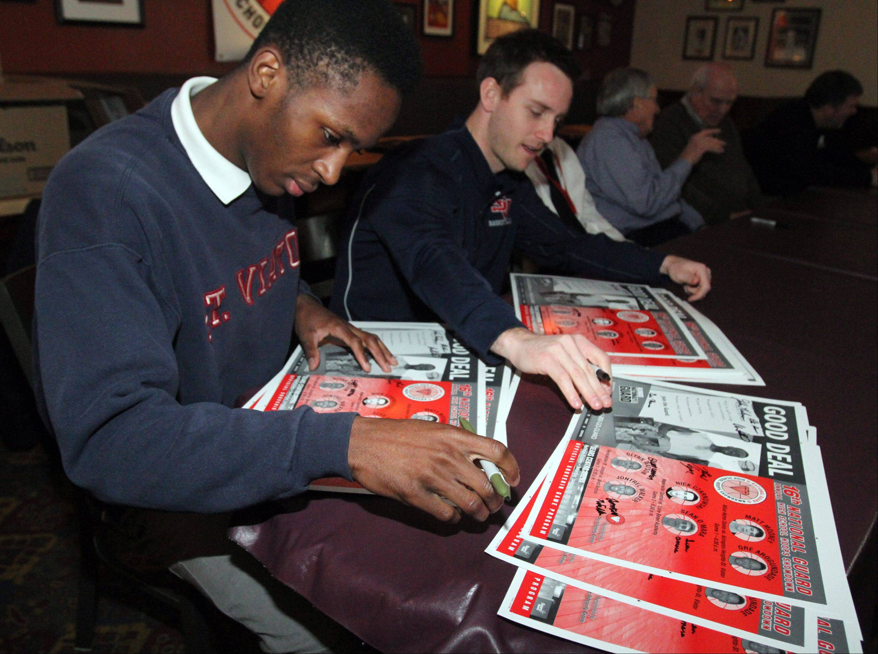 St. Viator basketball coach Mike Howland and guard Ore Arogundade sign posters during a news conference at Lou Malnati's Pizzeria in Schaumburg on Wednesday in advance of the National Guard High School Hoops Showdown on Saturday at the Sears Centre.