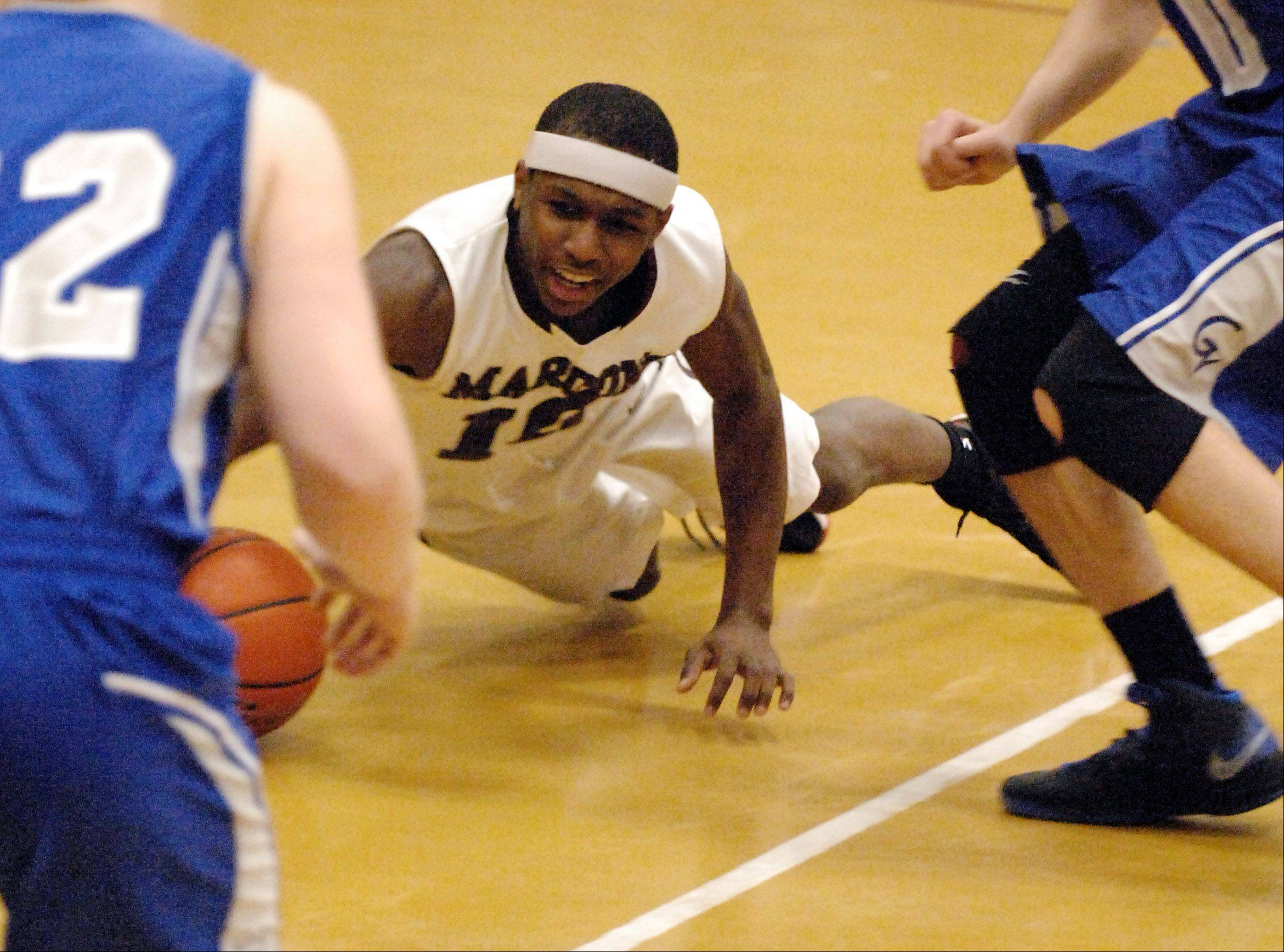 Elgin's Arie Williams dives for a loose ball against Geneva during Thursday's game in Elgin.