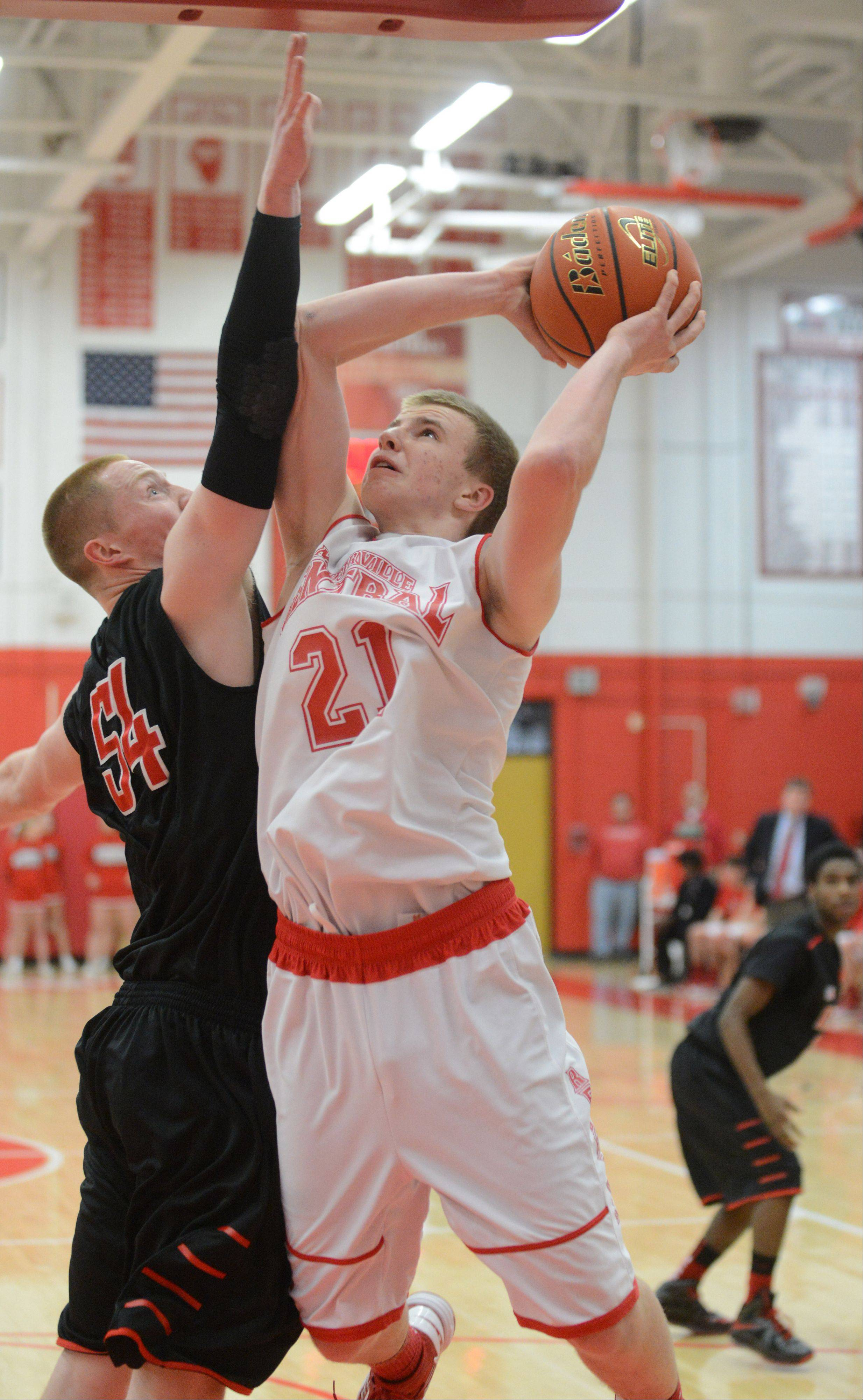 Brandon Havenga pf Glenbard East tries to block a shot from Mike Blaszczyk of Naperville Central during the Glenbard East at Naperville Central boys basketball game Friday.