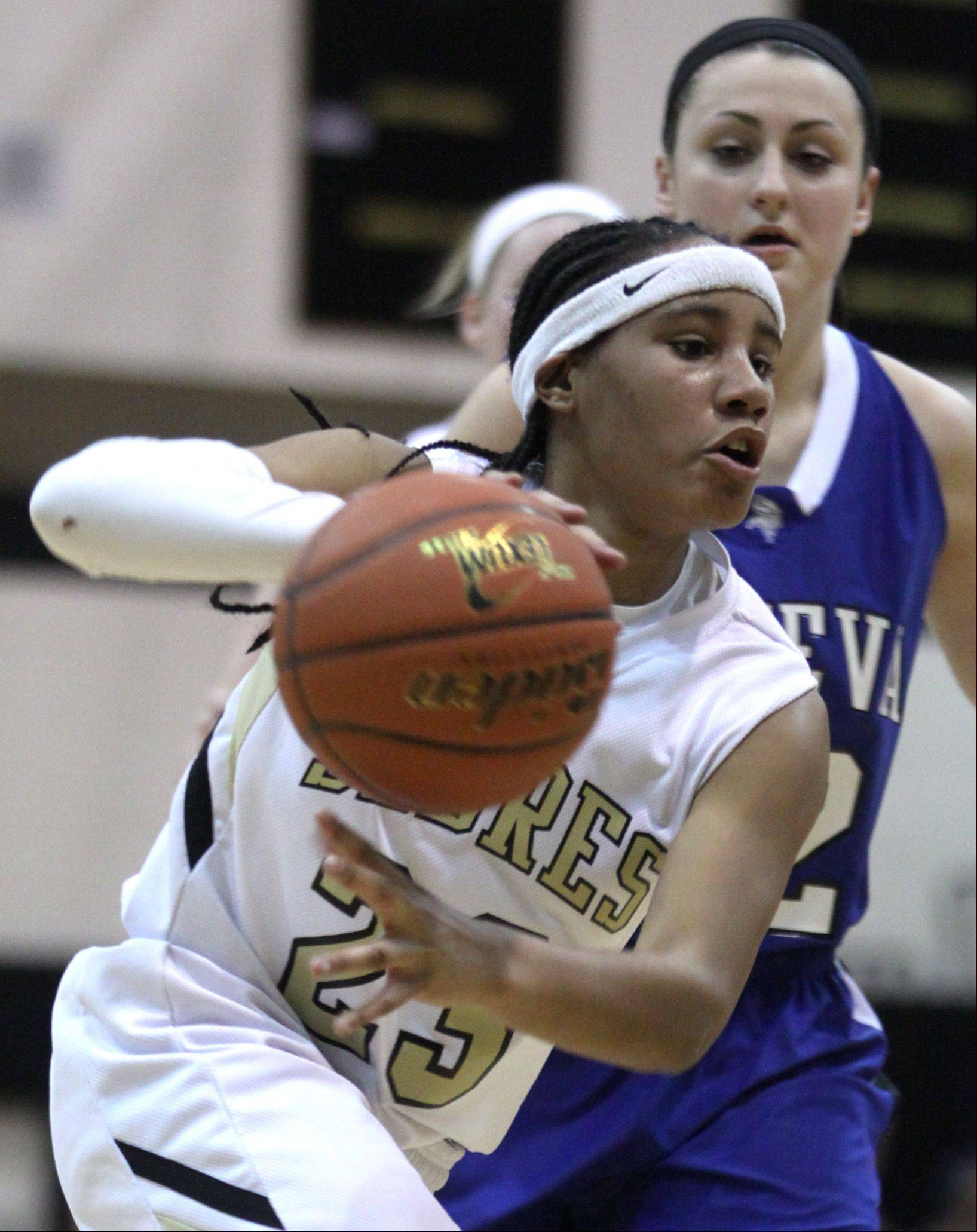 Streamwood's Deja Moore moves the ball past Geneva's Abby Novak during a varsity basketball game at Streamwood on Friday night. Geneva won the game 54-43.