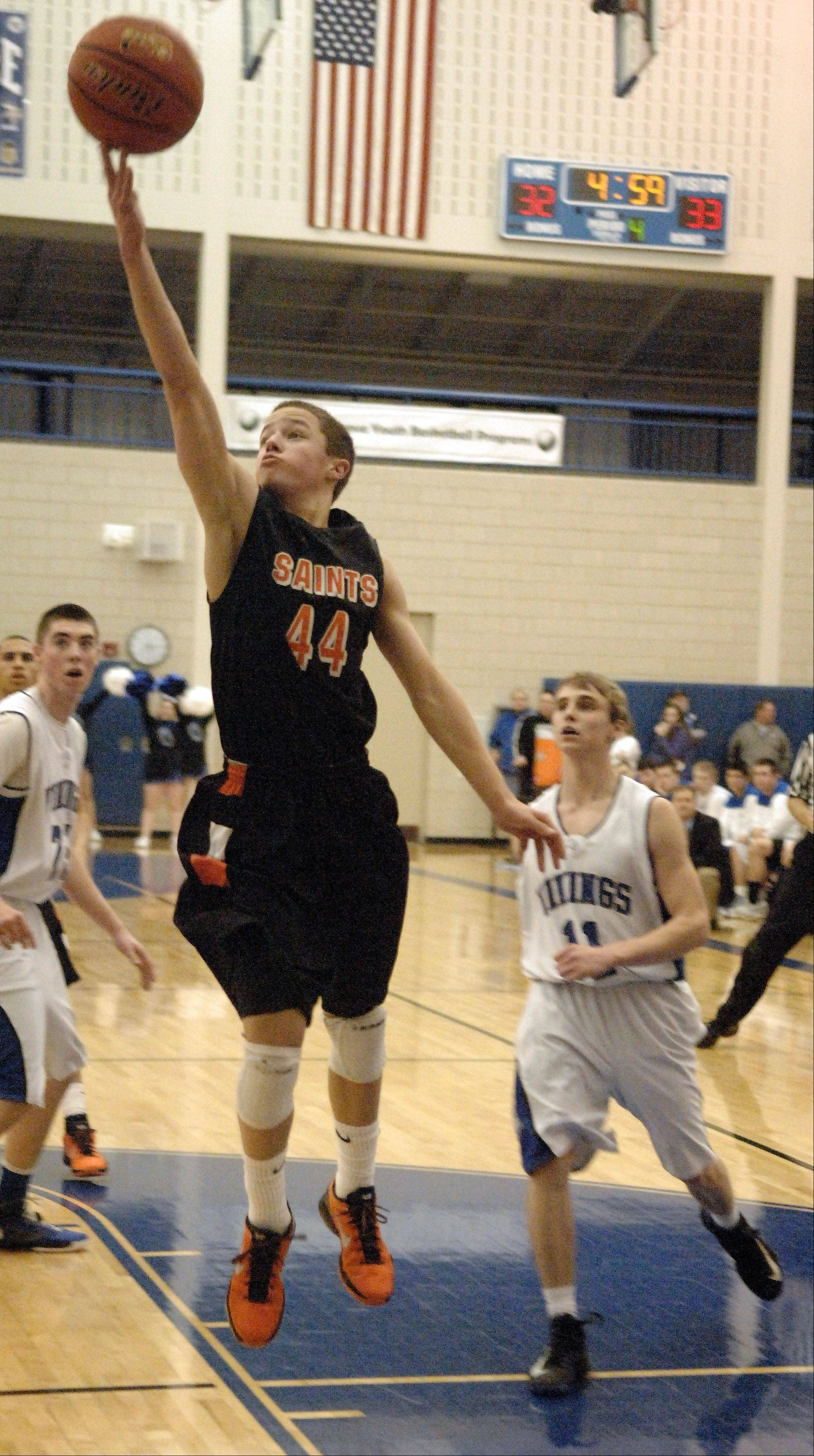 St. Charles East's Cole Gentry extends as he drives to the basket and scores.