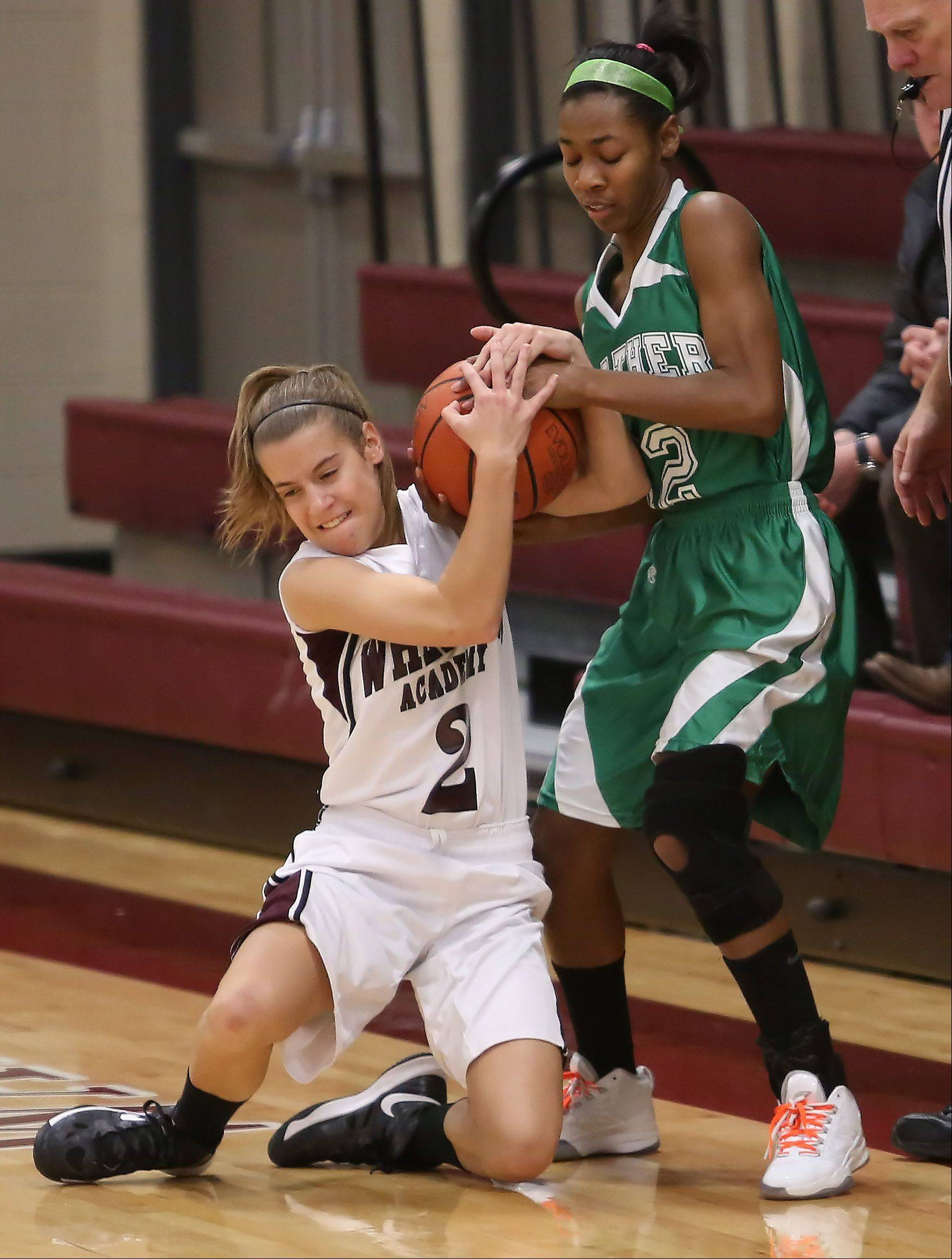Jamie Netzley, left, of Wheaton Academy and Anna Strong, right, of Walther Lutheran fight for the ball.