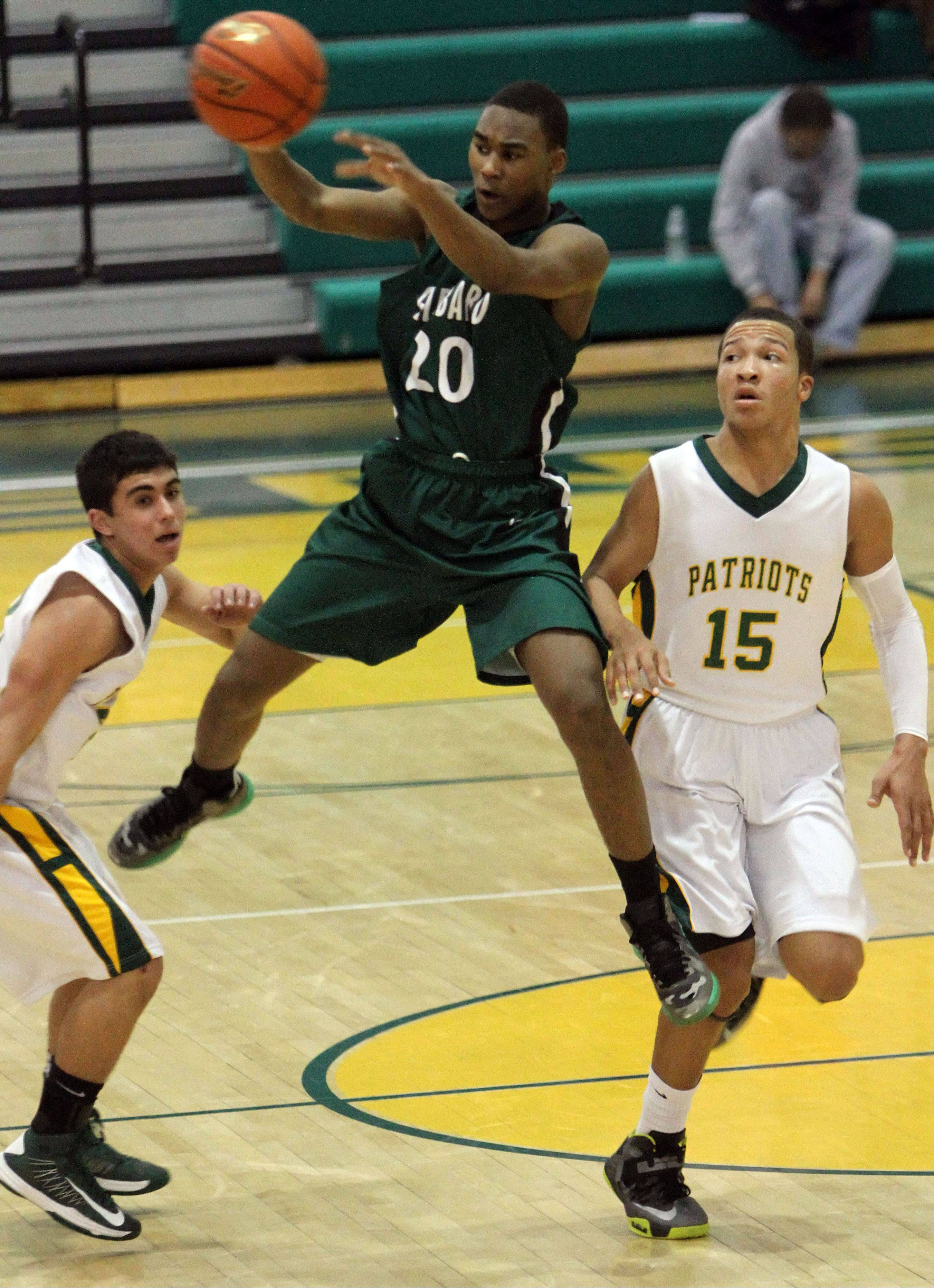 Glenbard West's Corey Davis passes with Stevenson's Justin Berkson, left, and Jalen Brunson defending Tuesday night in Lincolnshire.