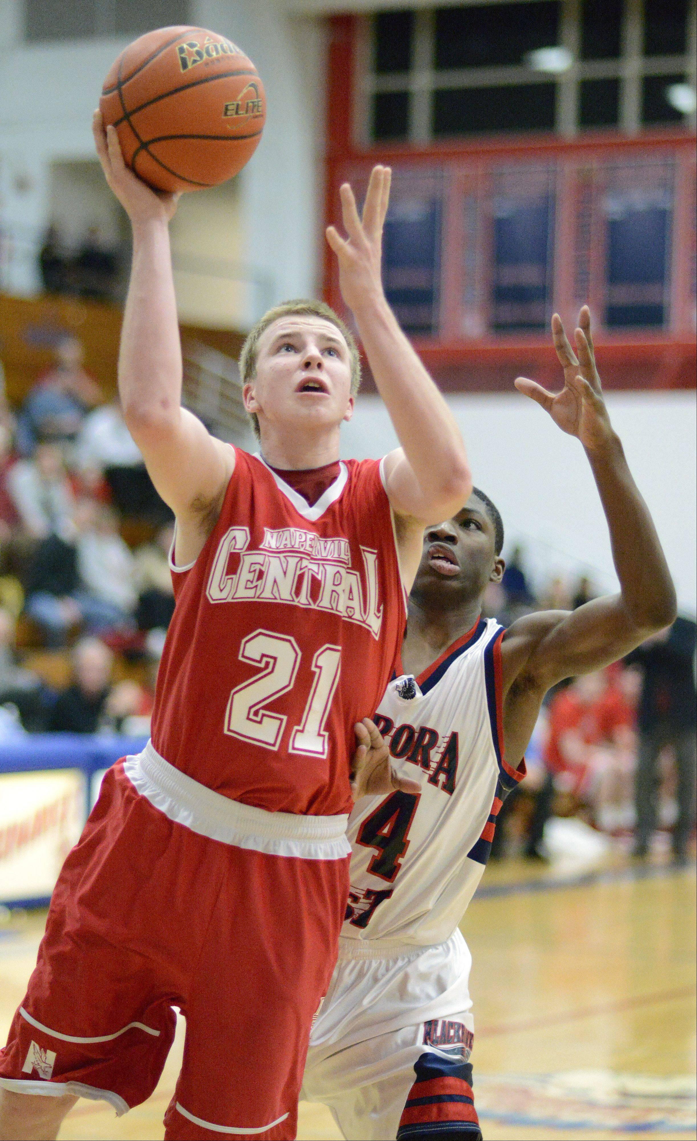 Naperville Central's Mike Blaszceyk shoots past West Aurora's Jayquan Lee in the first quarter on Tuesday, January 29.