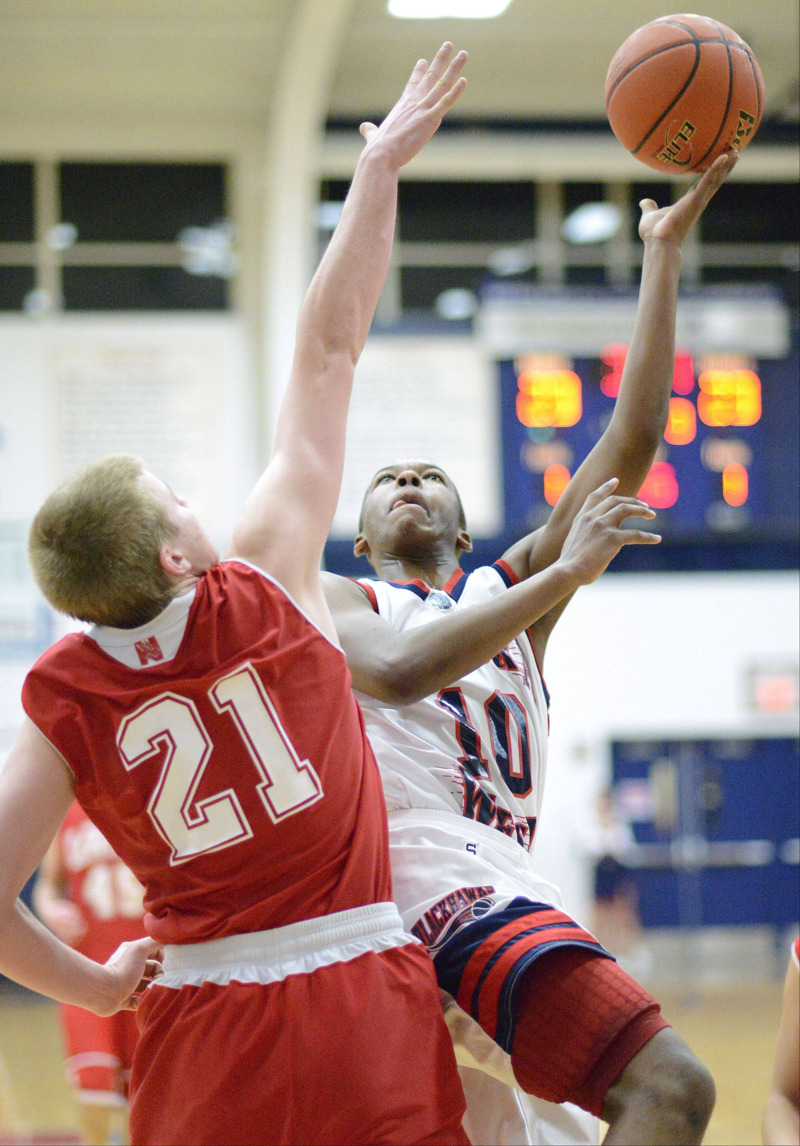 Naperville Central's Mike Blaszceyk attempts to block a shot by West Aurora's Jontrel Walker in the third quarter on Tuesday, January 29.