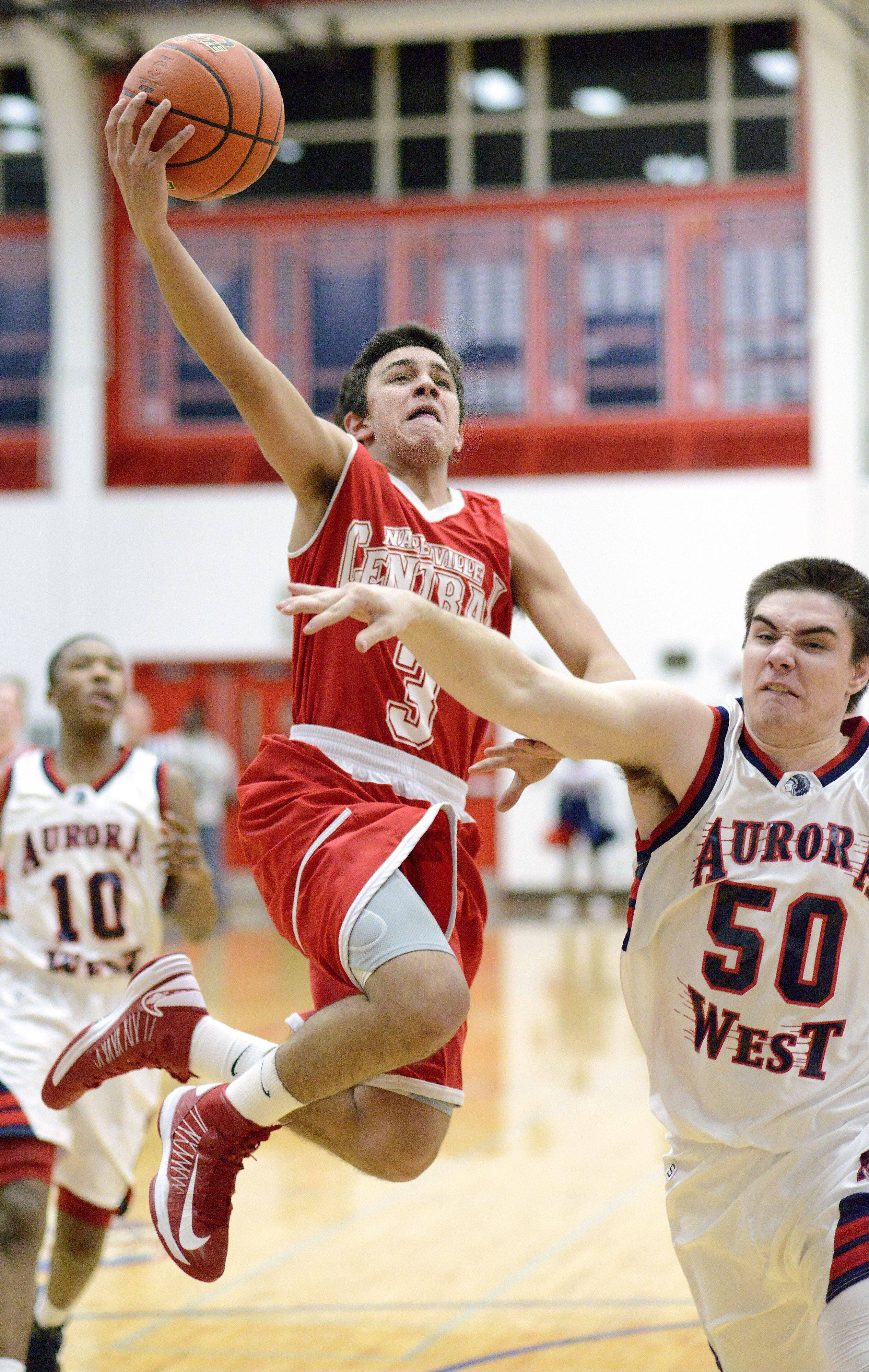 Naperville Central's Nicky Lopez flies overhead of West Aurora's Chandler Thomas in the first quarter on Tuesday, January 29.
