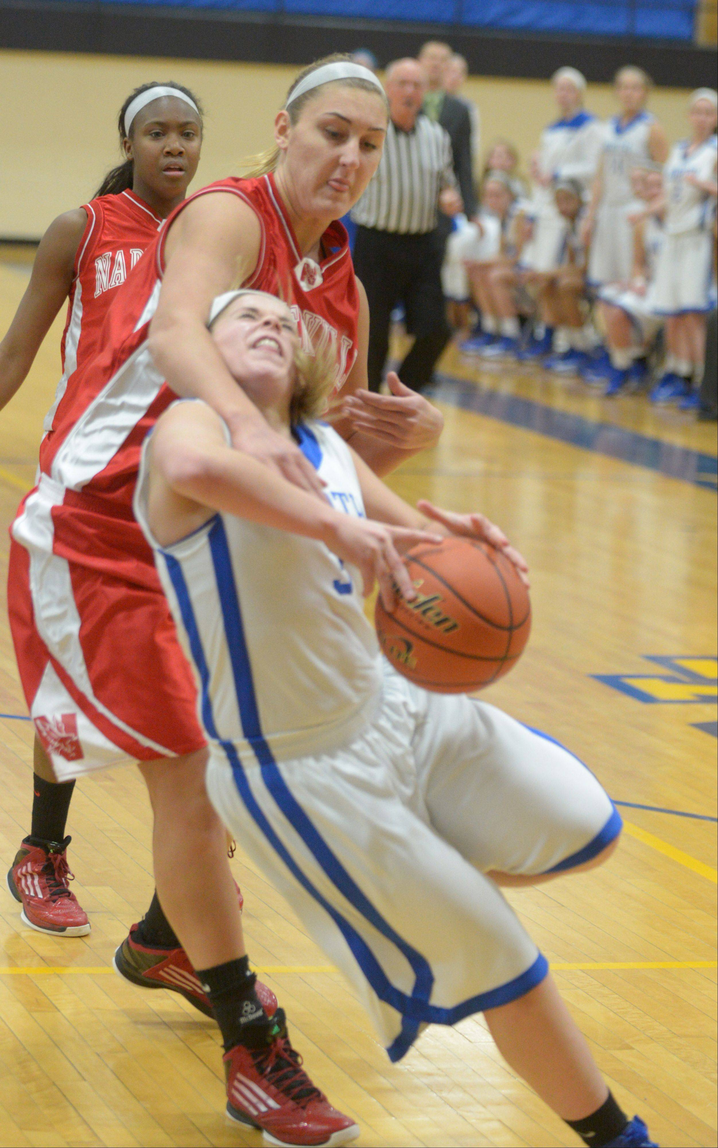 Victoria Trowbridge of Naperville central pulls down Reilly Stewart of Wheaton North during the Naperville Central at Wheaton North Girls basketball game Thursday.