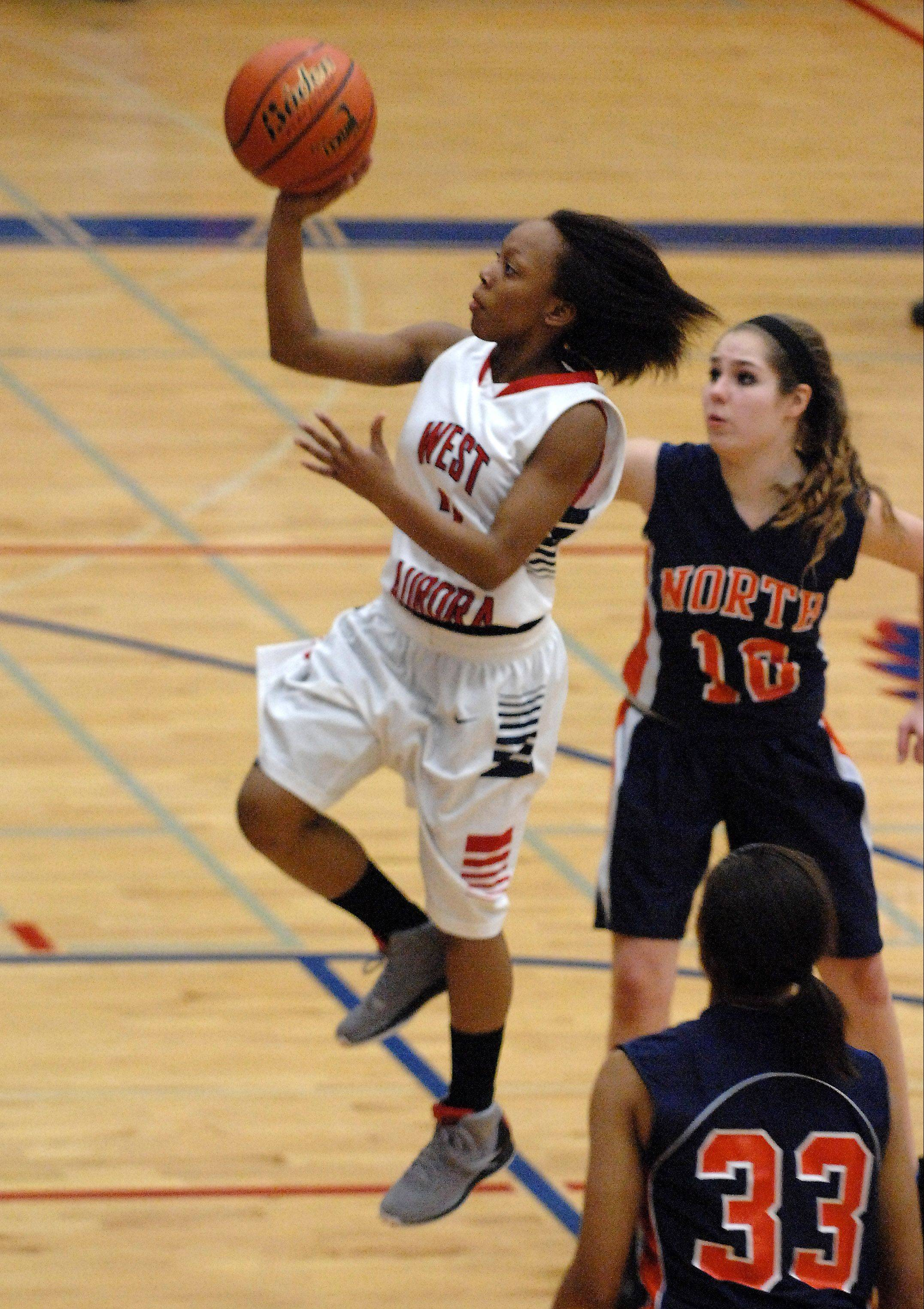 West Aurora's Alexis Wiggins pulls up with a running one-hander against Naperville North during Thursday's game in Aurora.