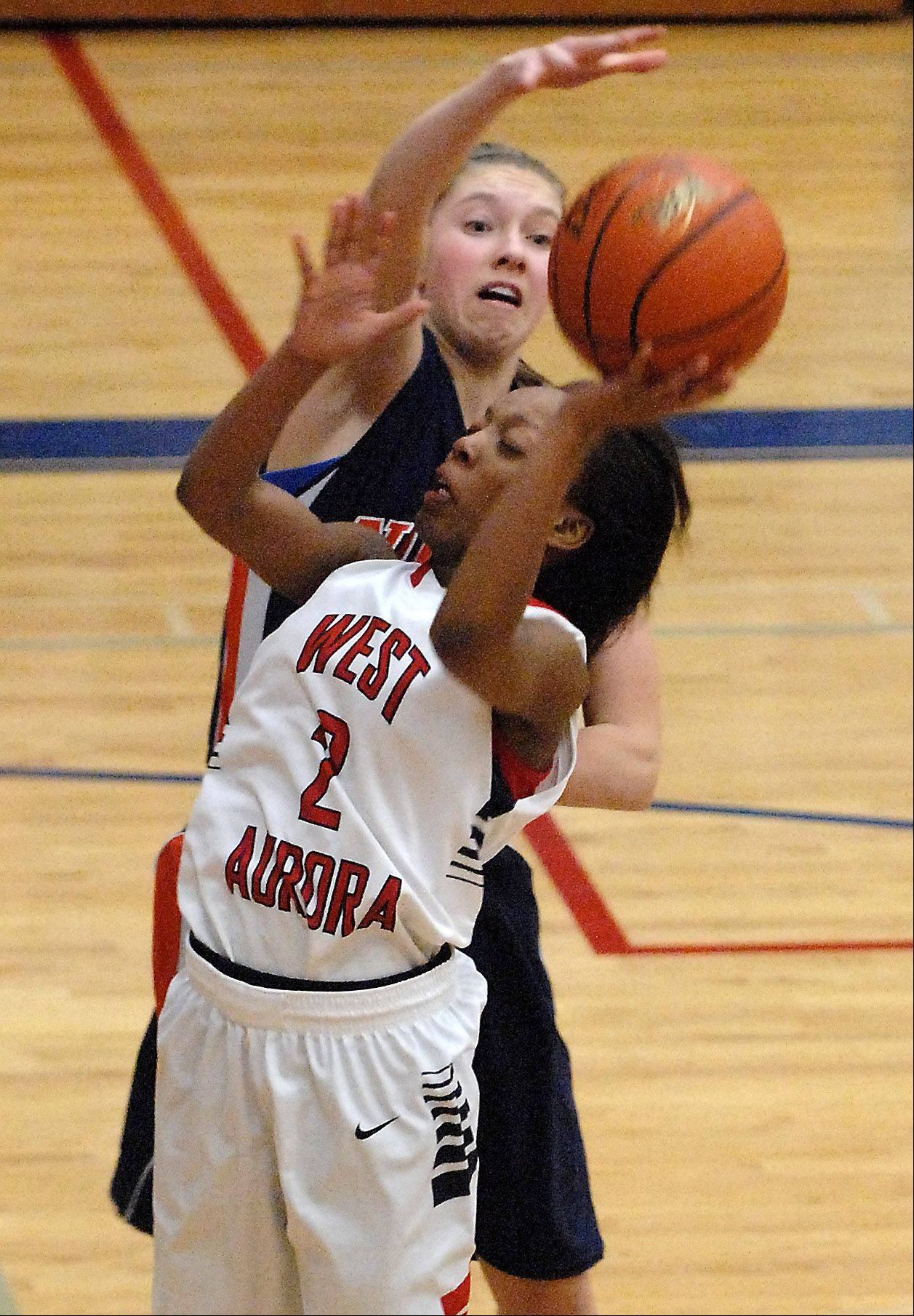West Aurora's Alexis Wiggins has her shot blocked by Naperville North's Katie Cores during Thursday's game in Aurora.