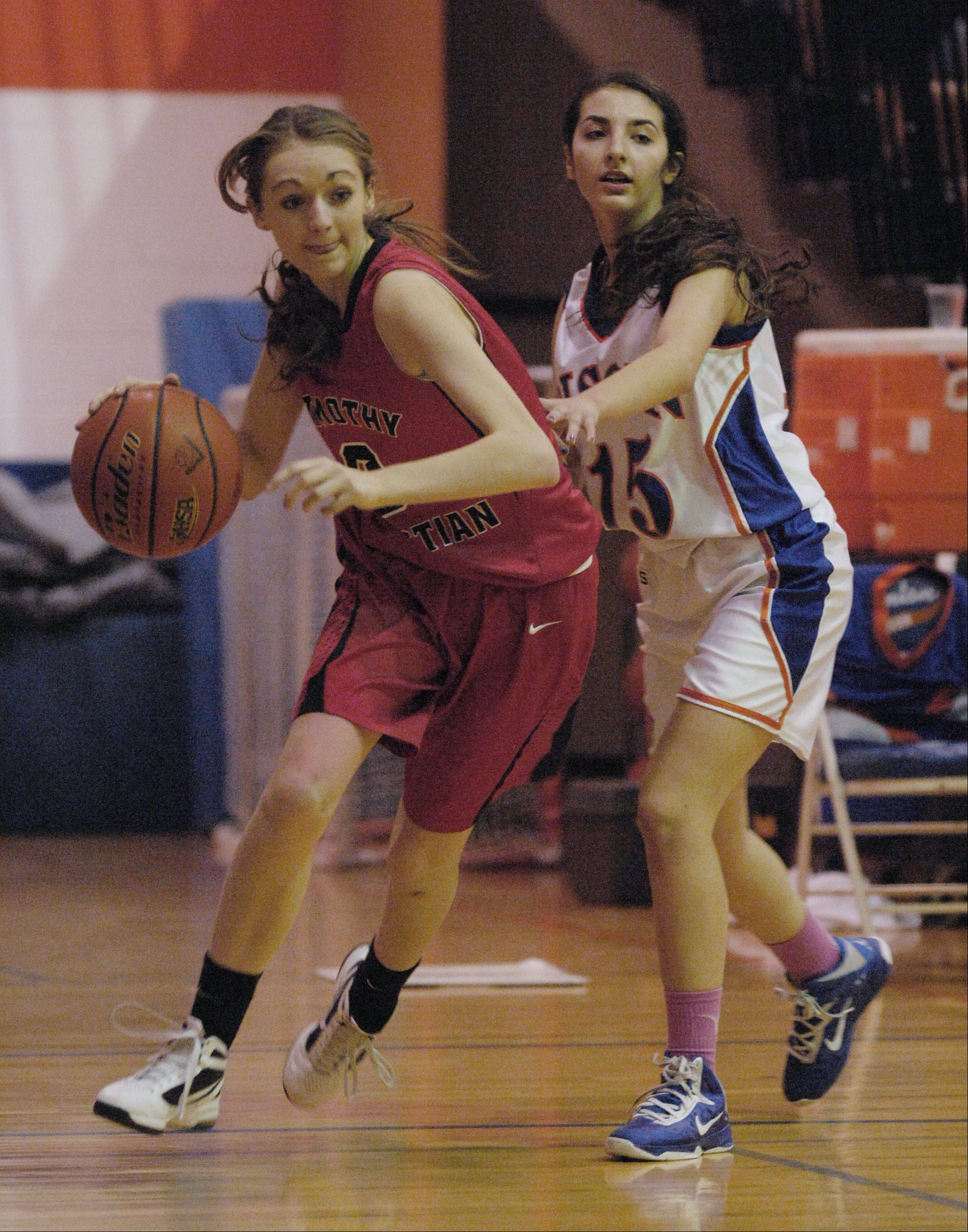 Brittany Scheidt of Timothy Christian drives past Tina Guarino of Fenton High School.