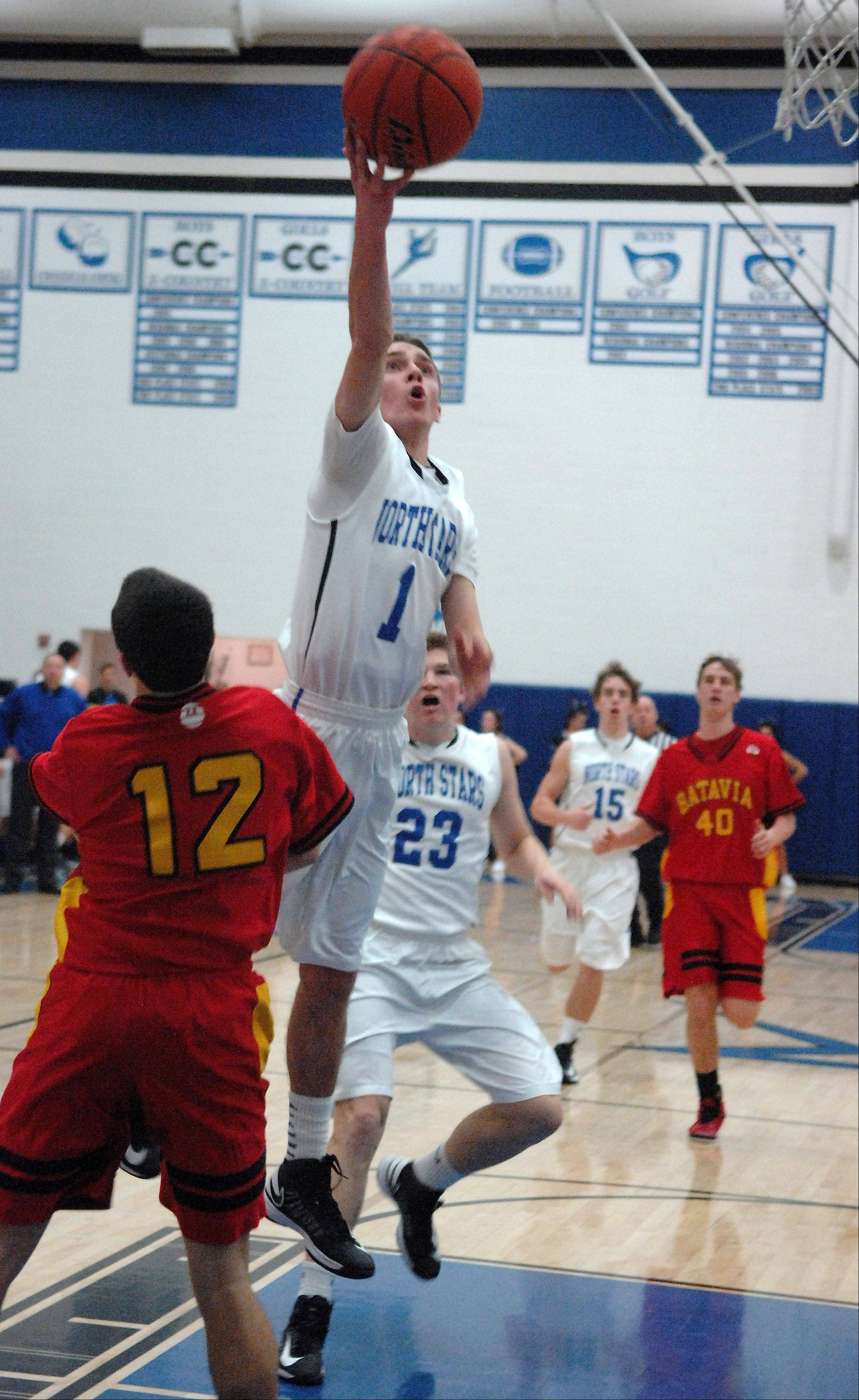 St. Charles North's Alec Goetz puts up a runner as he sails past Batavia's Jeremy Schoessling.