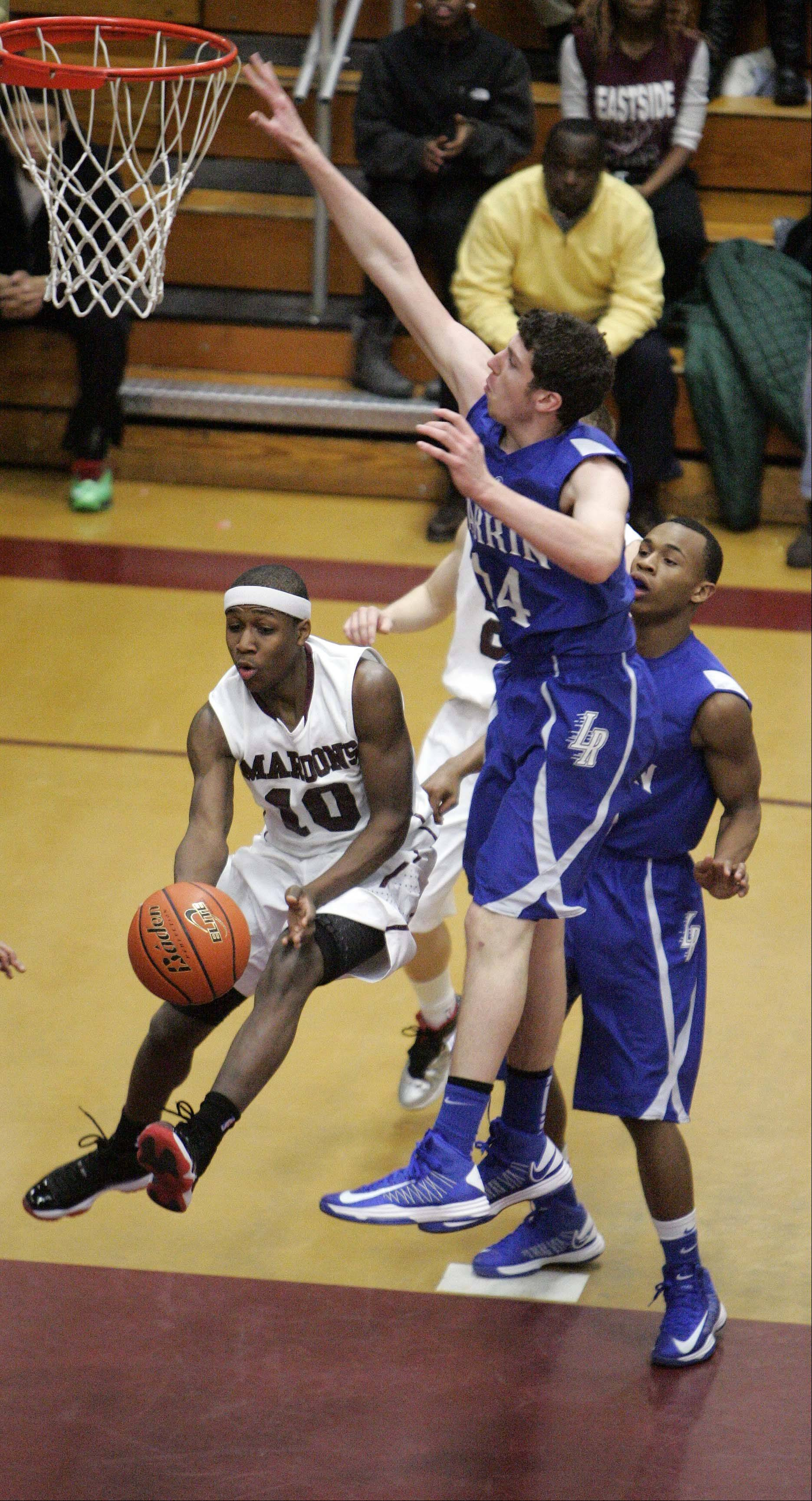 Elgin wing Arie Williams (10) looks for an opening after going to the hoop Friday night at Chesbrough Field House. Larkin's Drew Jones defends.
