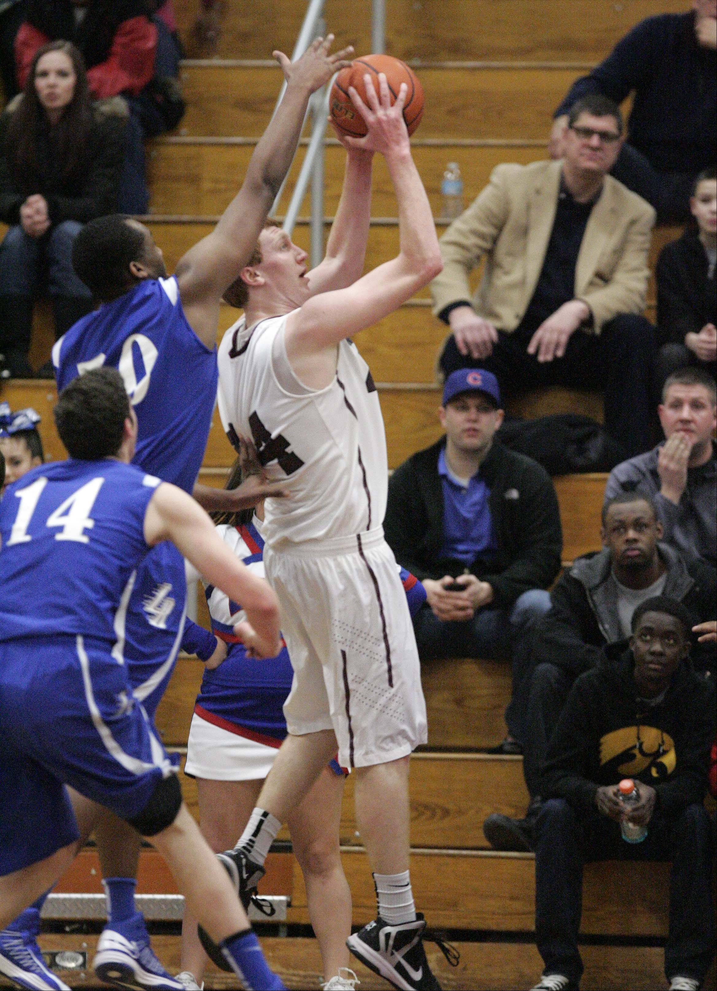 Larkin's Daniel McFadden (50) tries to get a hand on Elgin post Eric Sedlack's shot Friday night at Chesbrough Field House.