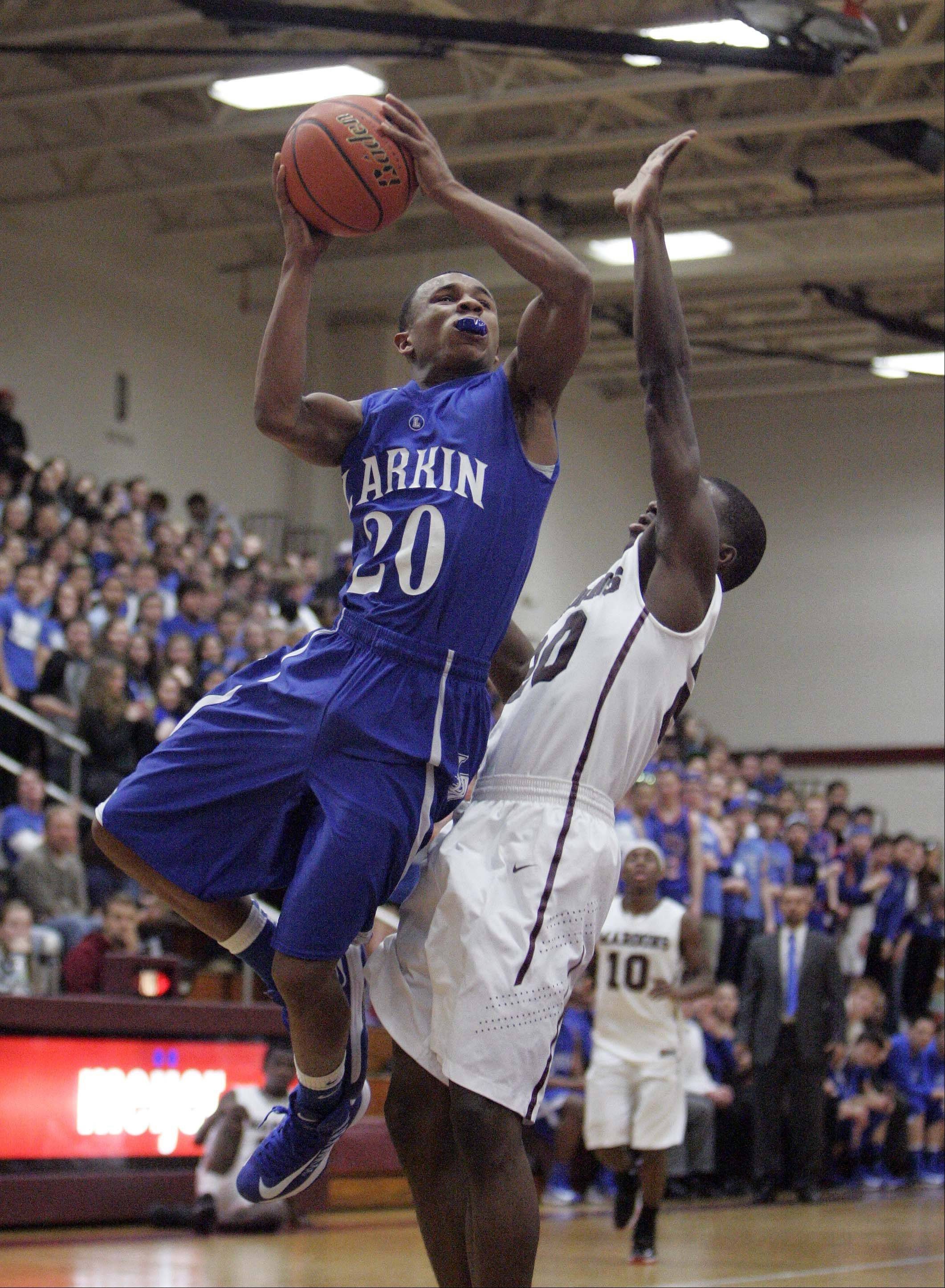 Larkin's Quentin Ruff (20) goes strong to the hoop past Elgin's Isaiah Butler Friday night at Chesbrough Field House.