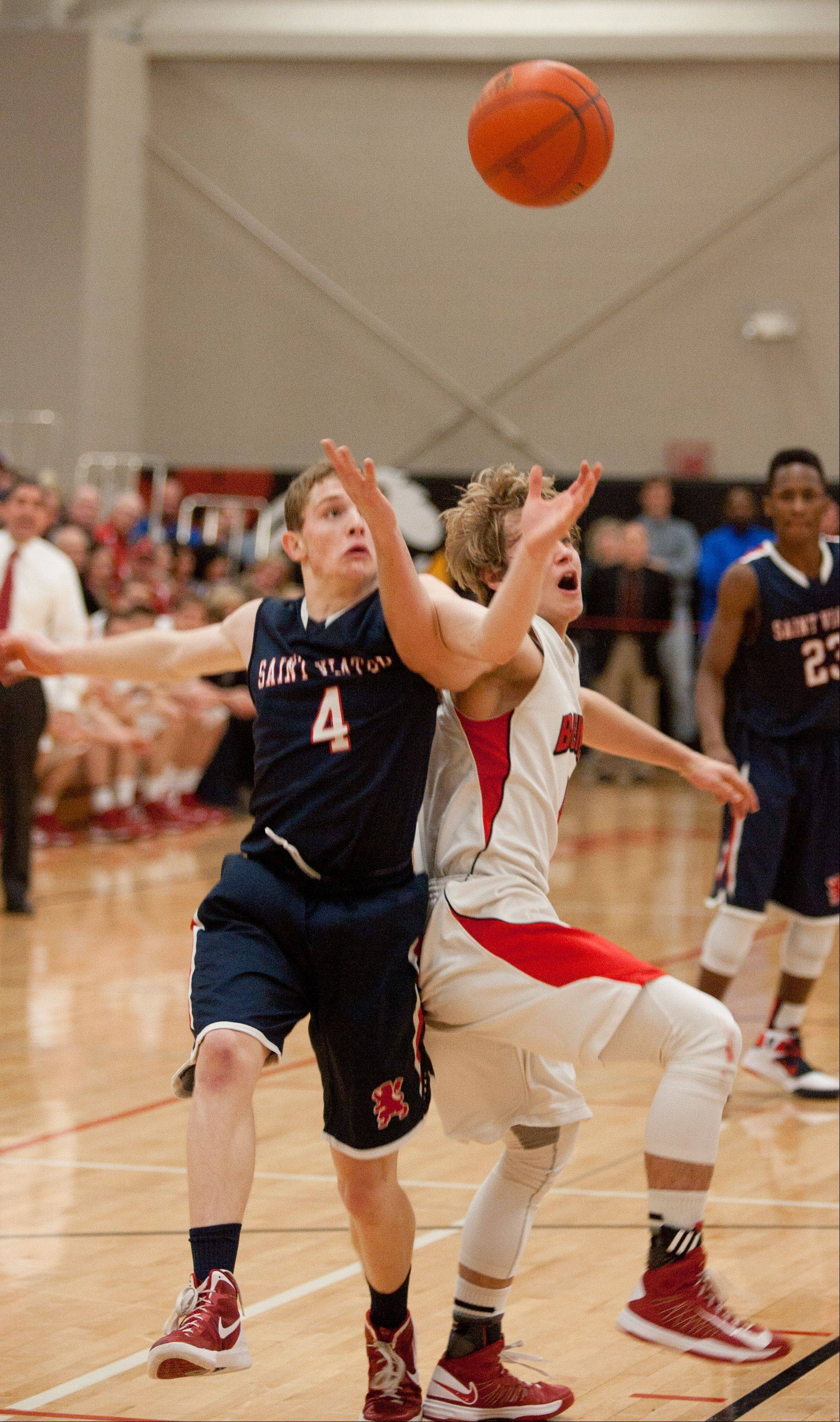 St. Viator's Kevin Hammarlund, left, battles Benet's Eddie Eshoo, right, during boys basketball action in Lisle.