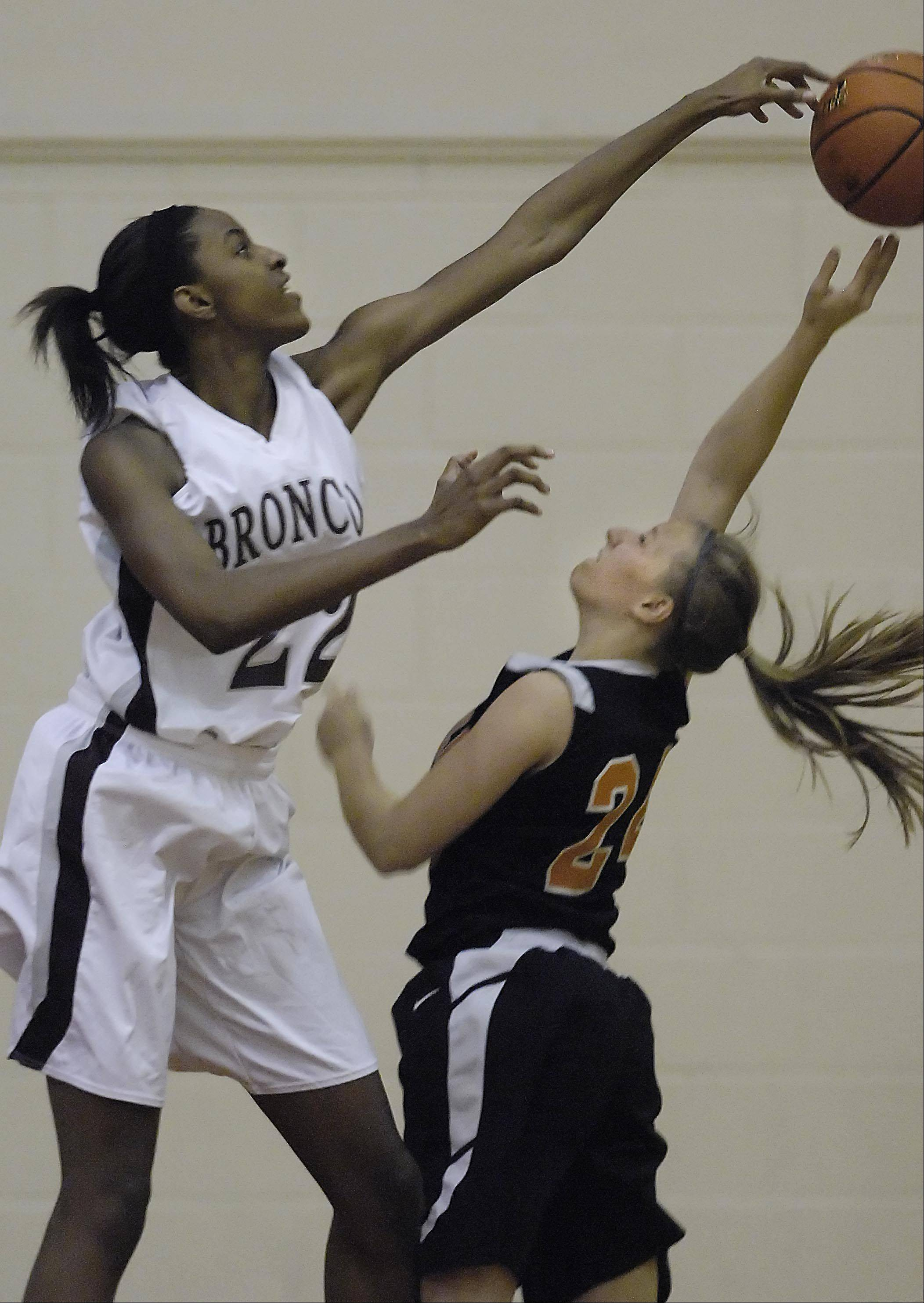 Montini's Malayna Johnson blocks a shot by St. Charles East's Laney Deckrow Thursday at the Lady Saxon Tournament in Schaumburg.